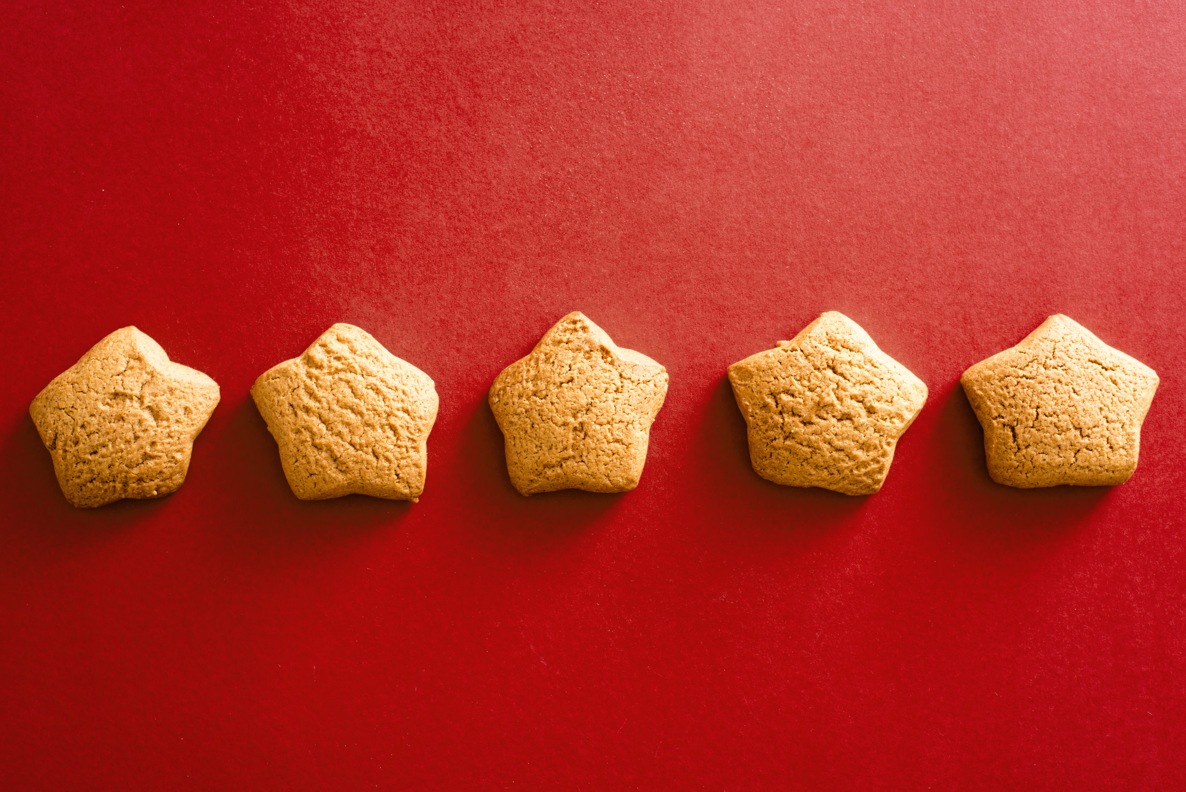 Five home baked star shaped cookies on a plain red background with copy space.