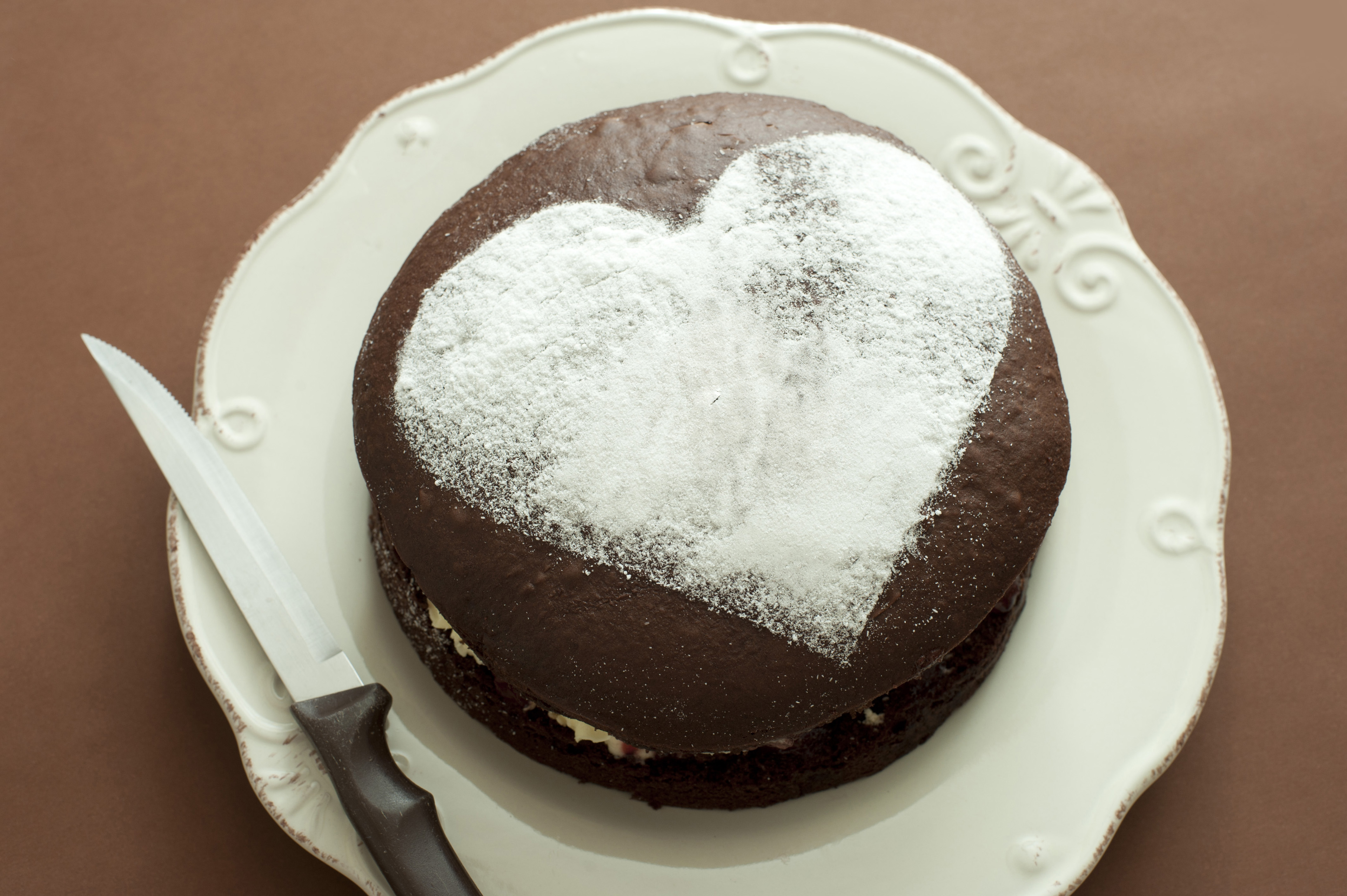 Close up Valentine Brown Cake on Plate with Heart Shape on Top. Isolated on Brown Background.