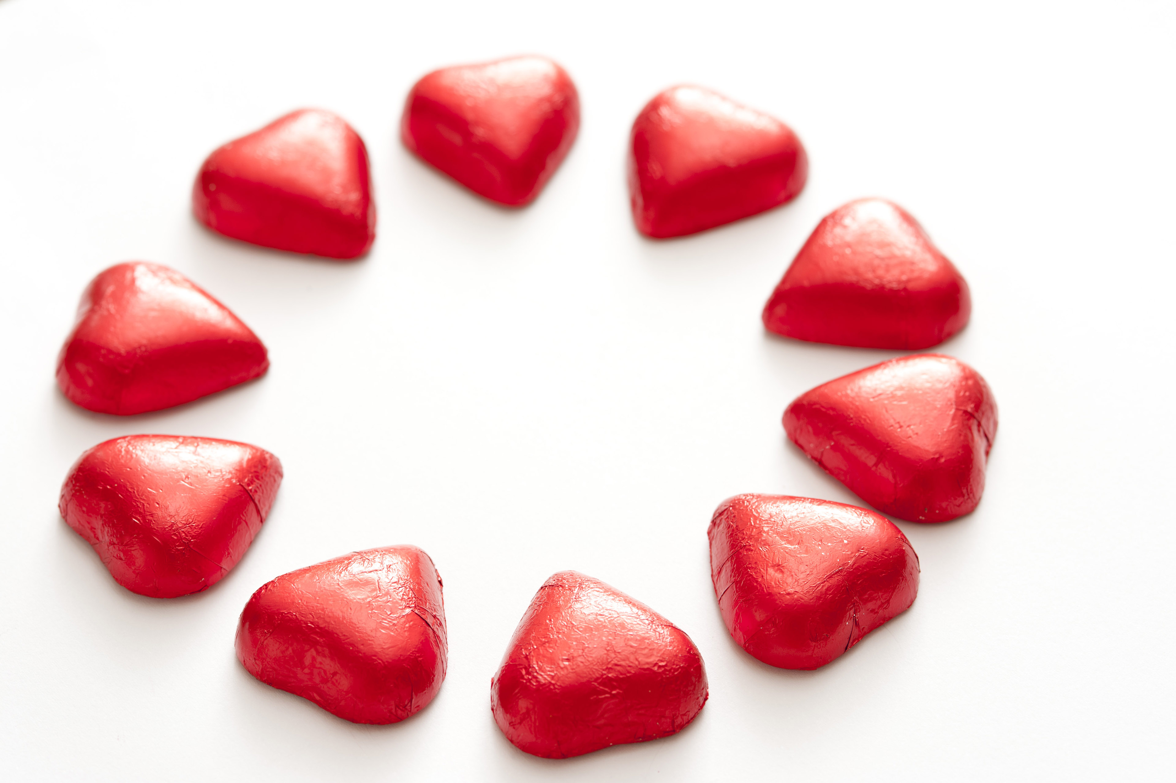Ten bright red valentine hearts arranged in a circle isolated on a plain white background.