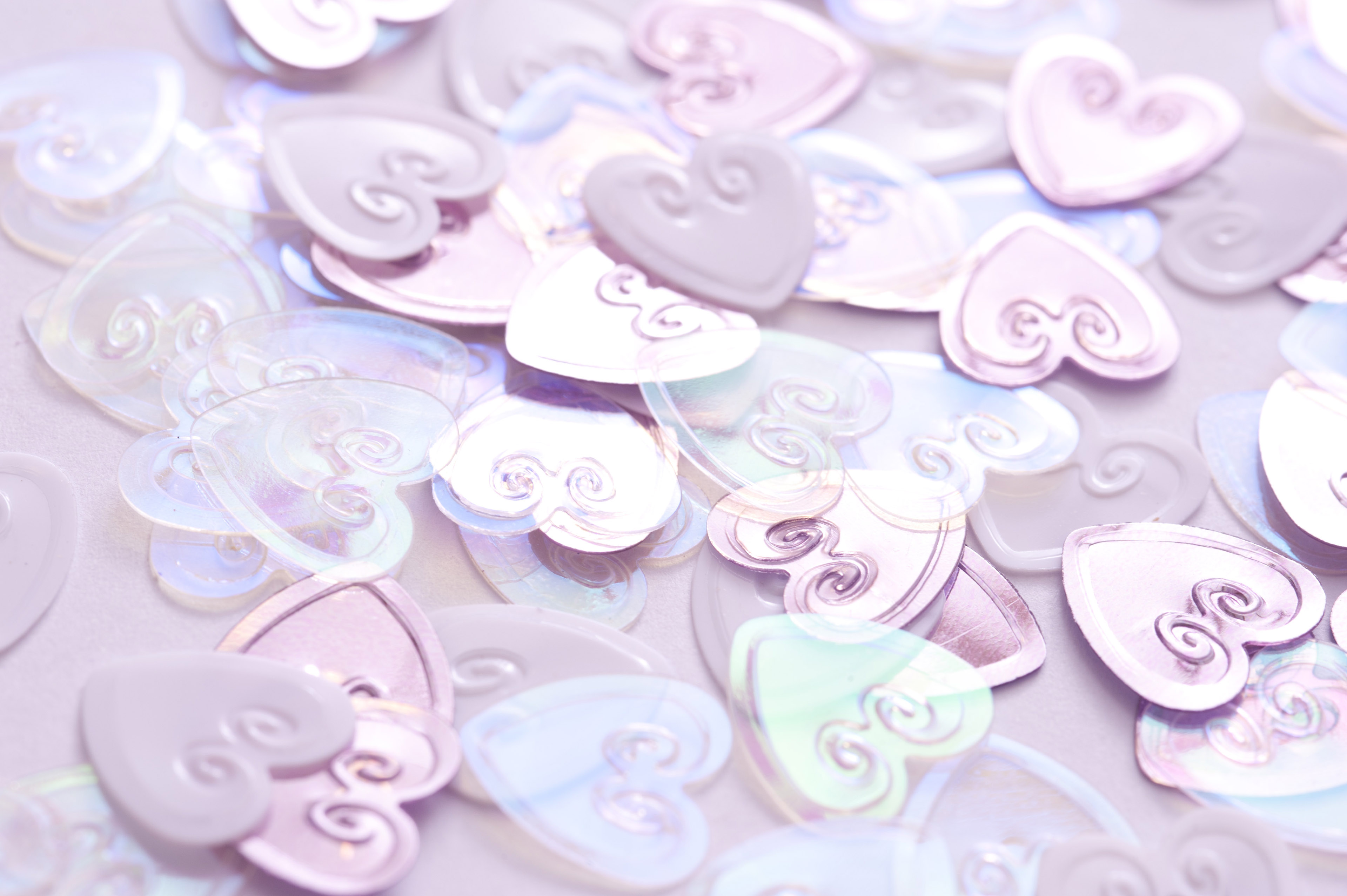 A pile of pink, metallic wedding heart decorations in a dreamy background.