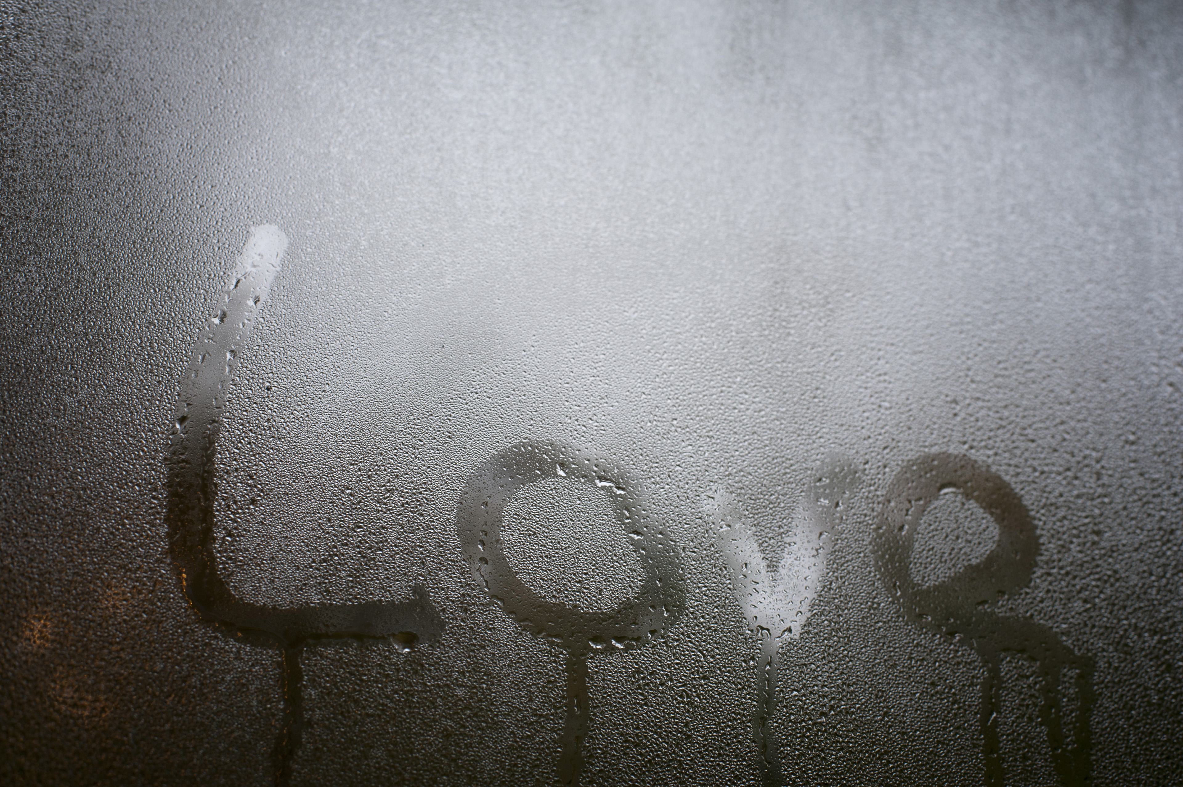 Close up Love Texts on Misty Glass Window for Backgrounds, Emphasizing Copy Space.