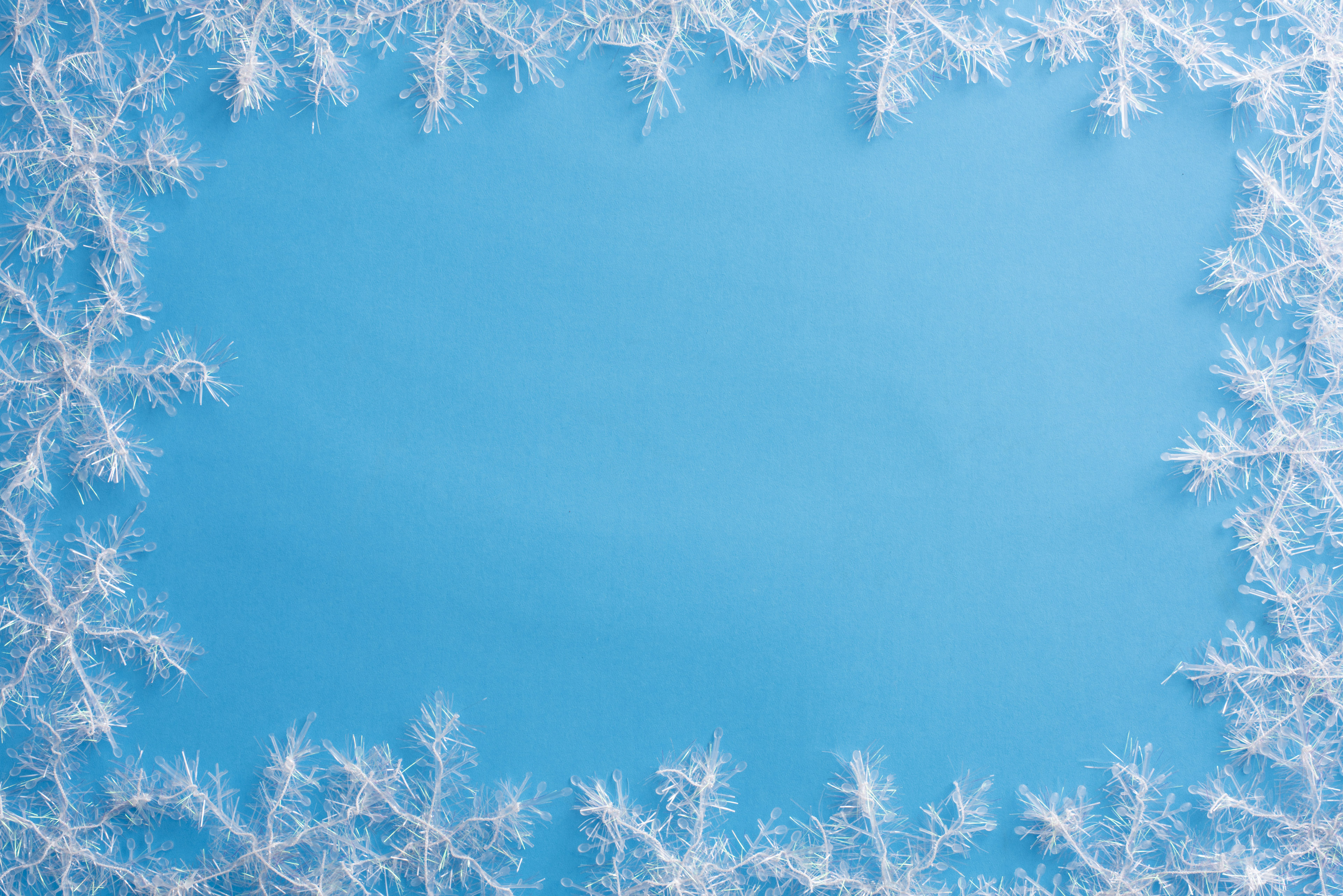 A white winter, snowflake edged, rectangular frame isolated on a plain blue background with copy space.