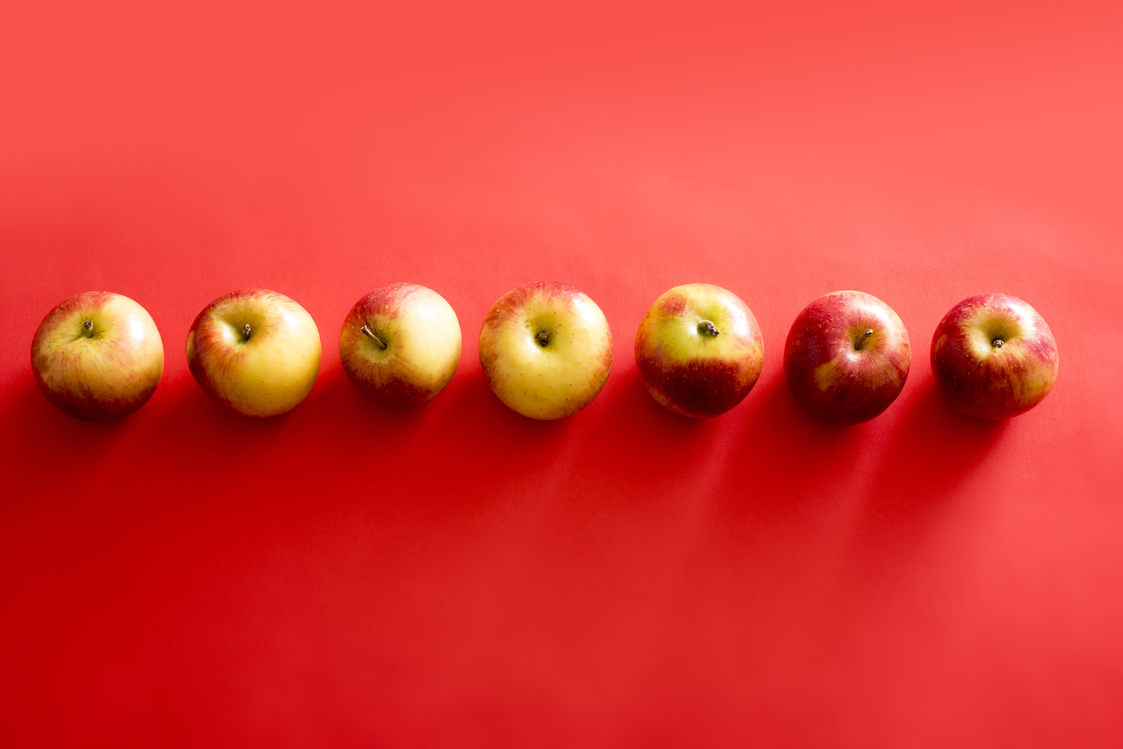 Seven apples seen from above arranged in line against red background