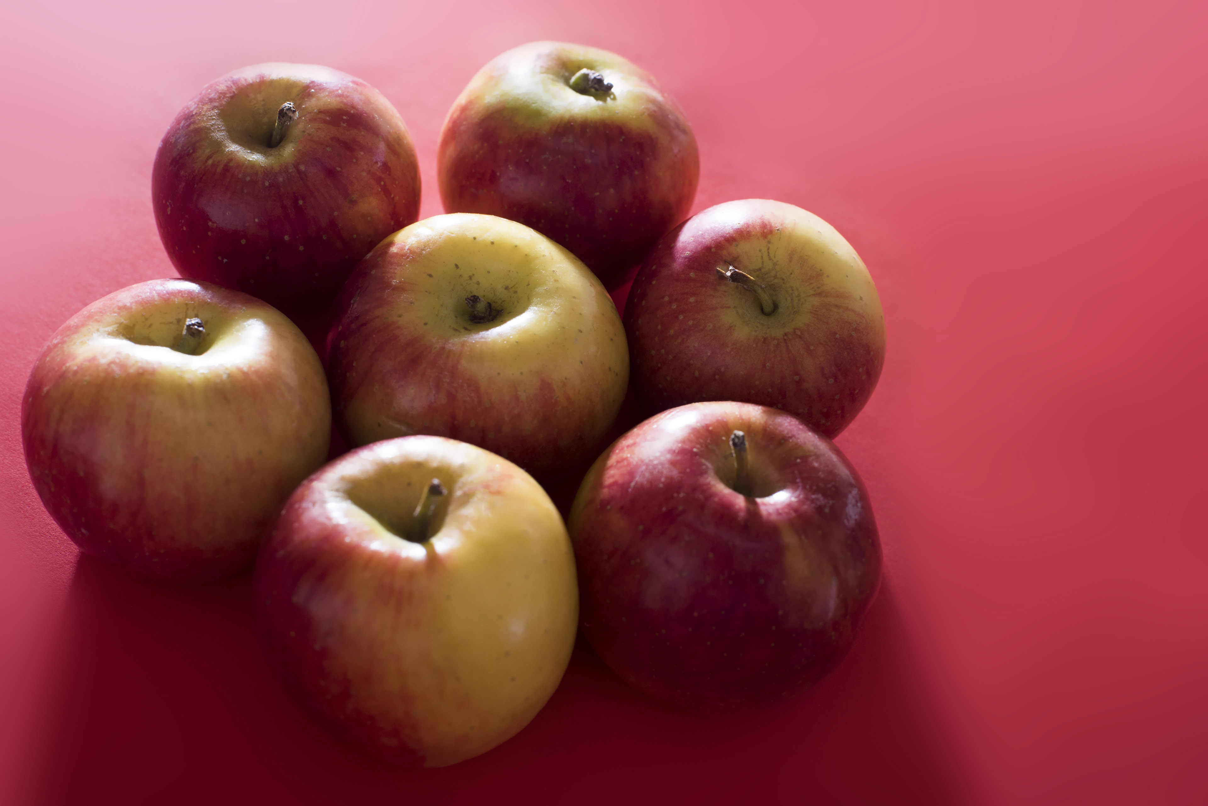 A group of seven apples huddled together lit by bright, contrasting light on a plain red background with copy space.
