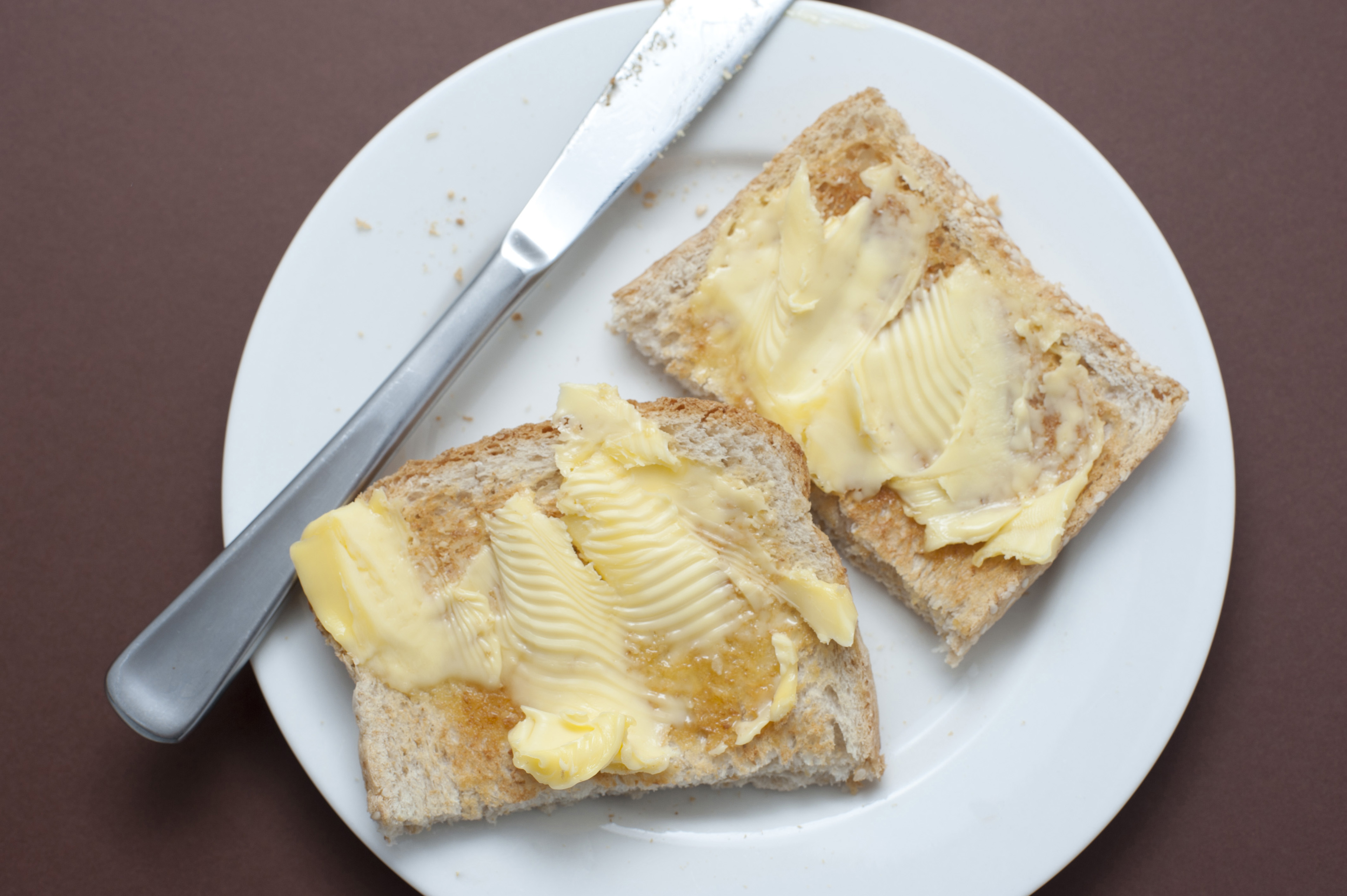 Two slices of fresh buttered white toast with a bread knife served on a plate for morning breakfast, overhead view