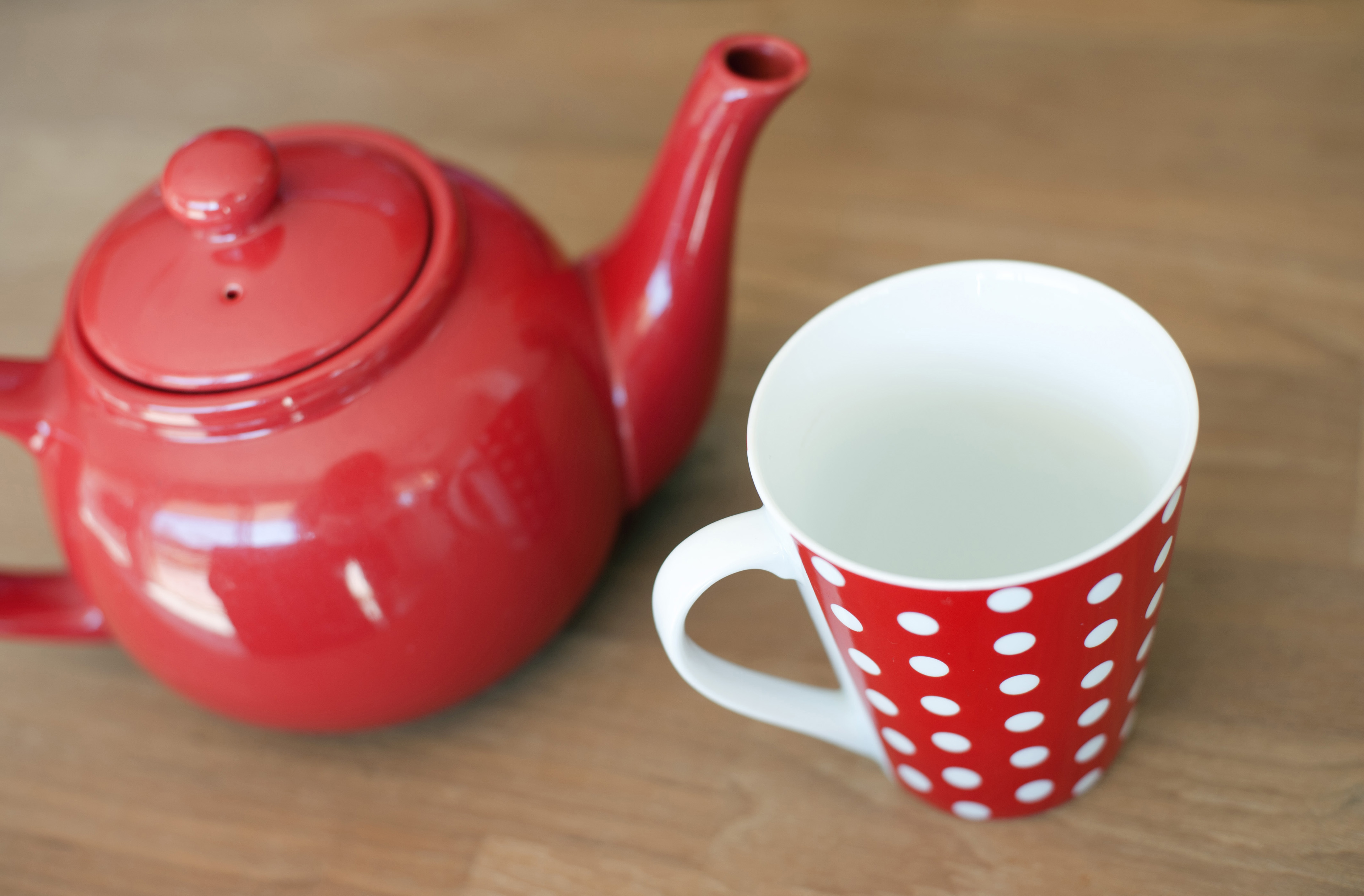 High angle view of a colorful red polka dot ceramic mug and teapot on a brown background