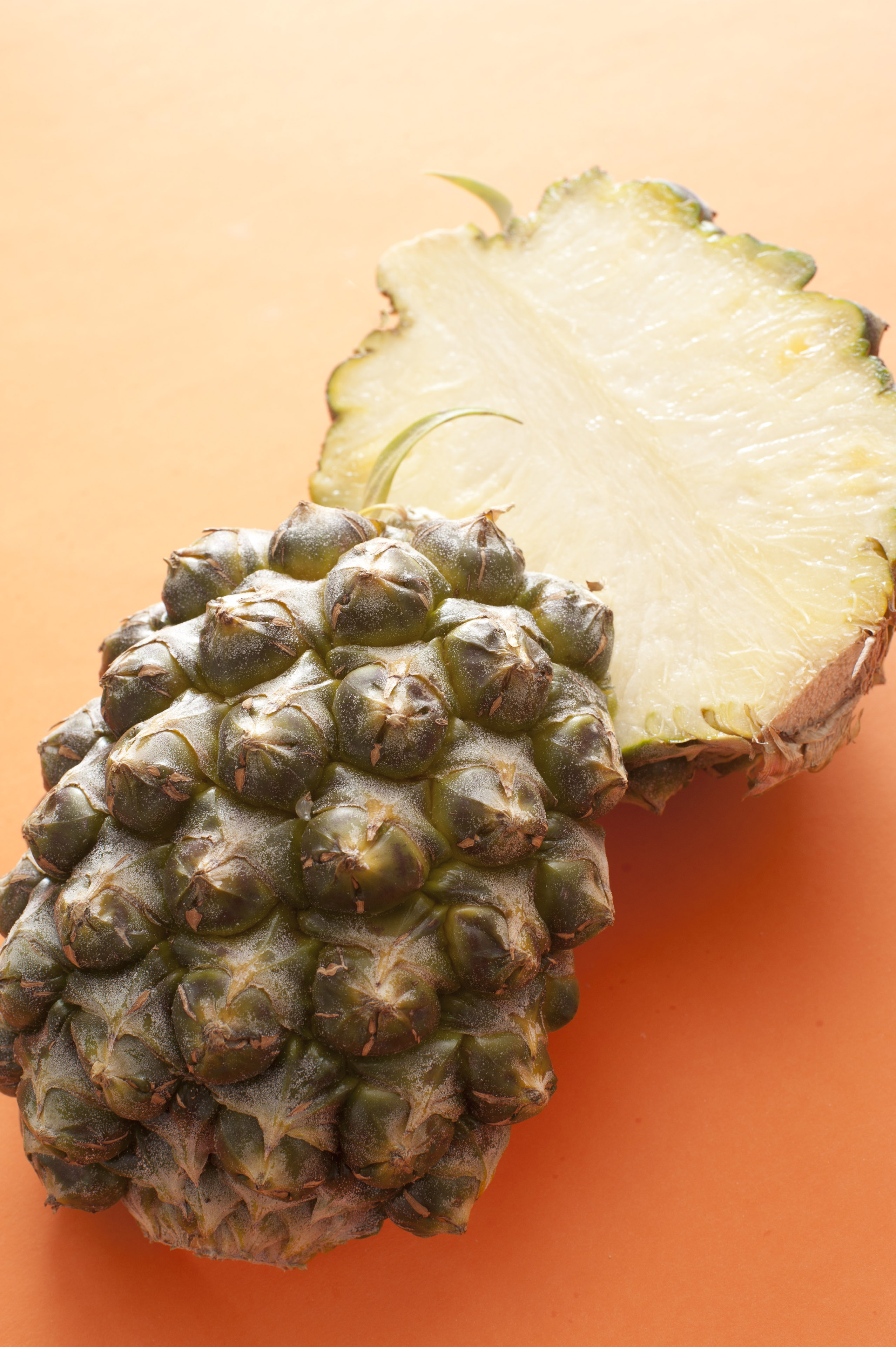 A fresh pineapple cut in half and isolated on a bright orange background with copy space.