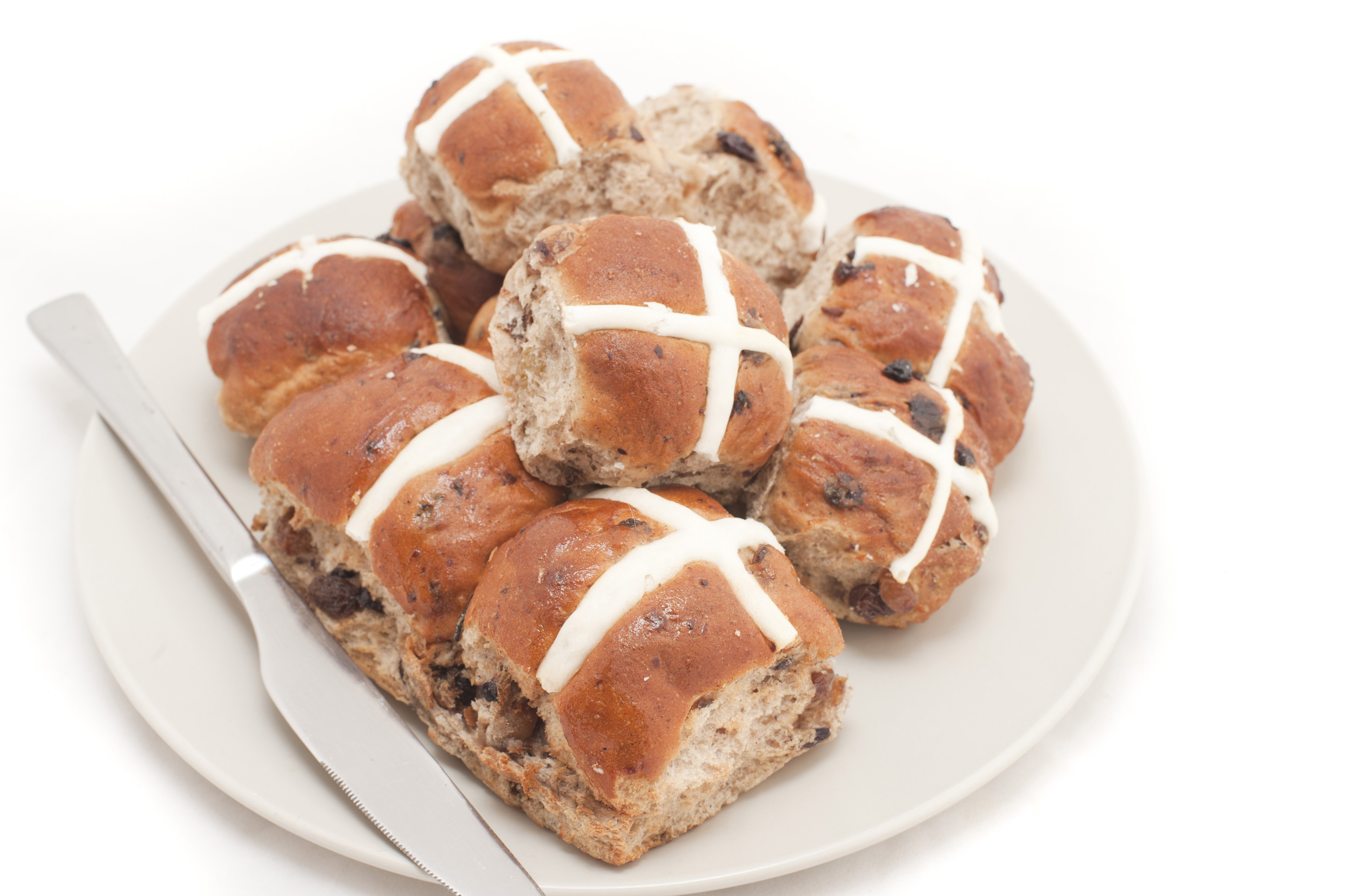 Plate of freshly baked spicy fruity Hot Cross Buns with raisins symbolic of the crucifixion of Christ at Easter