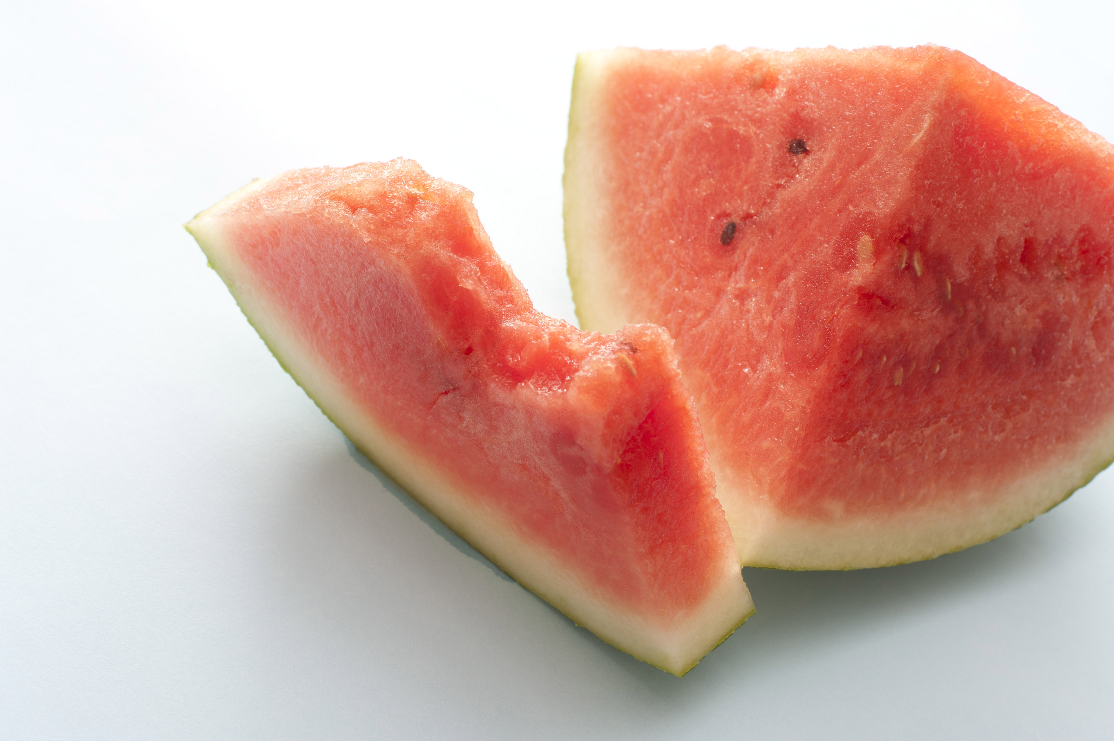Half eaten slice of fresh juicy watermelon over a white background for a healthy refreshing summer snack