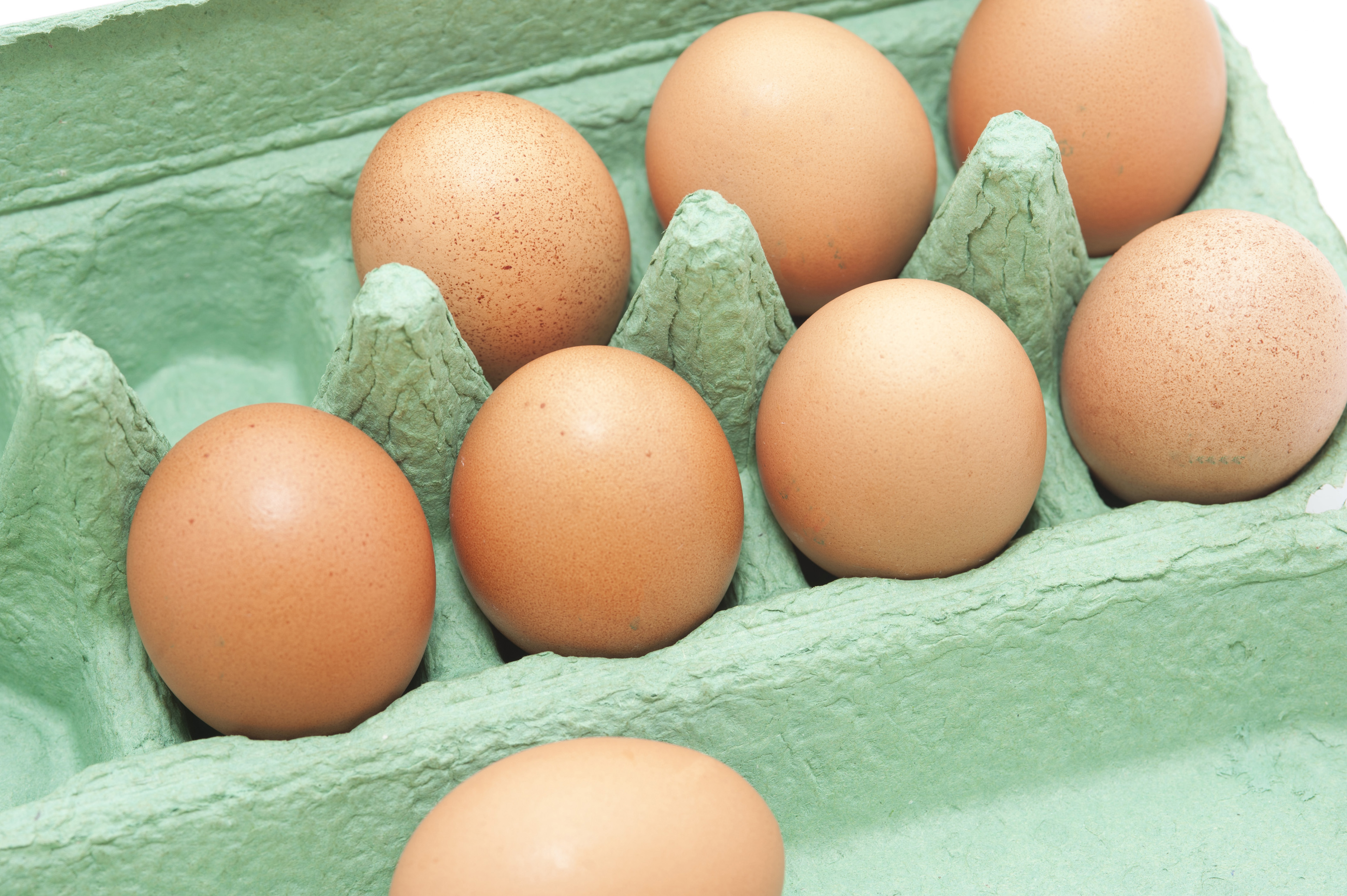 Fresh brown hens eggs in a cardboard carton retail packaging , high angle view of the open box