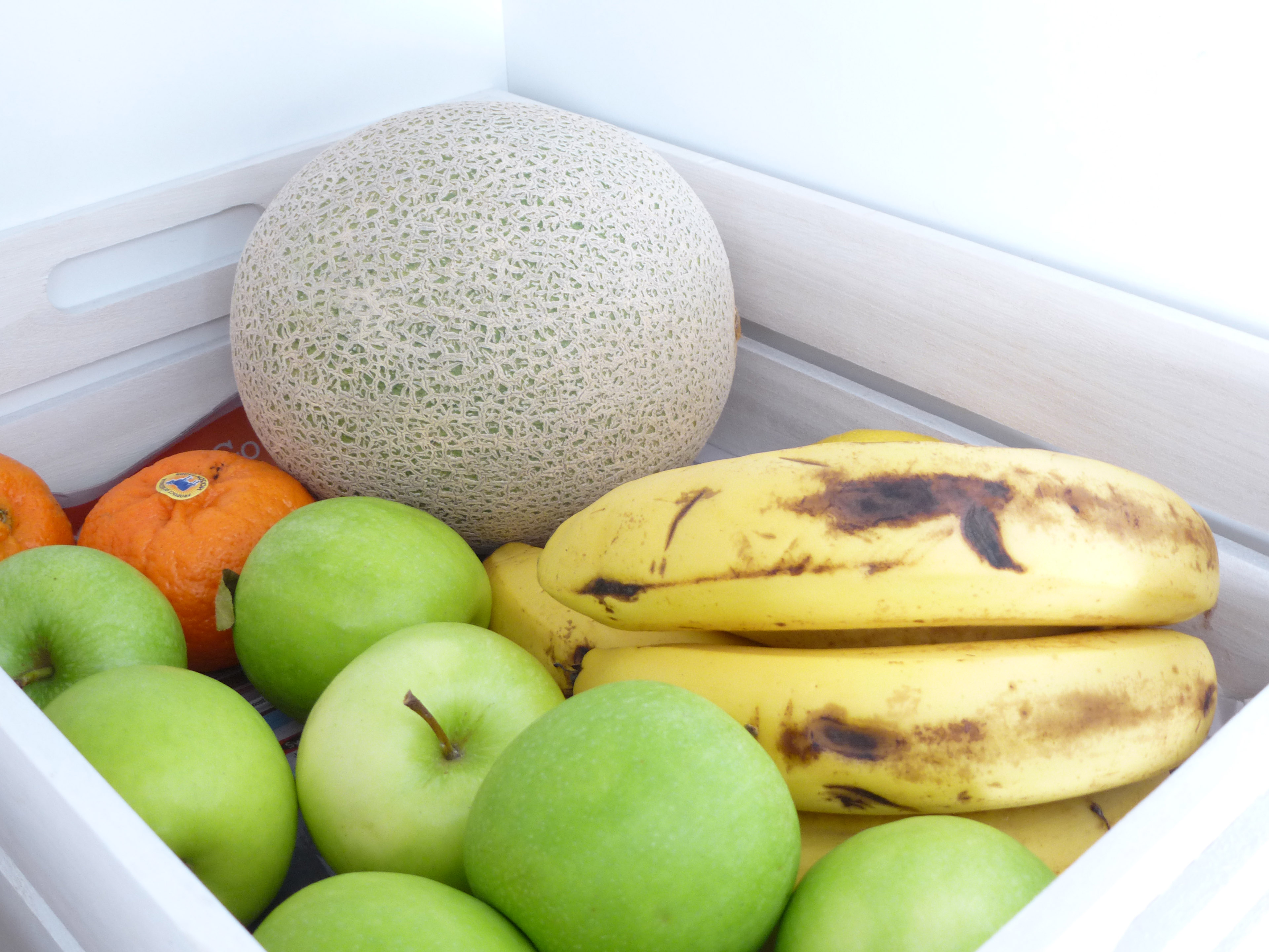 A wooden market crate filled with vibrant healthy fruits including apples, bananas, oranges and rock melon.