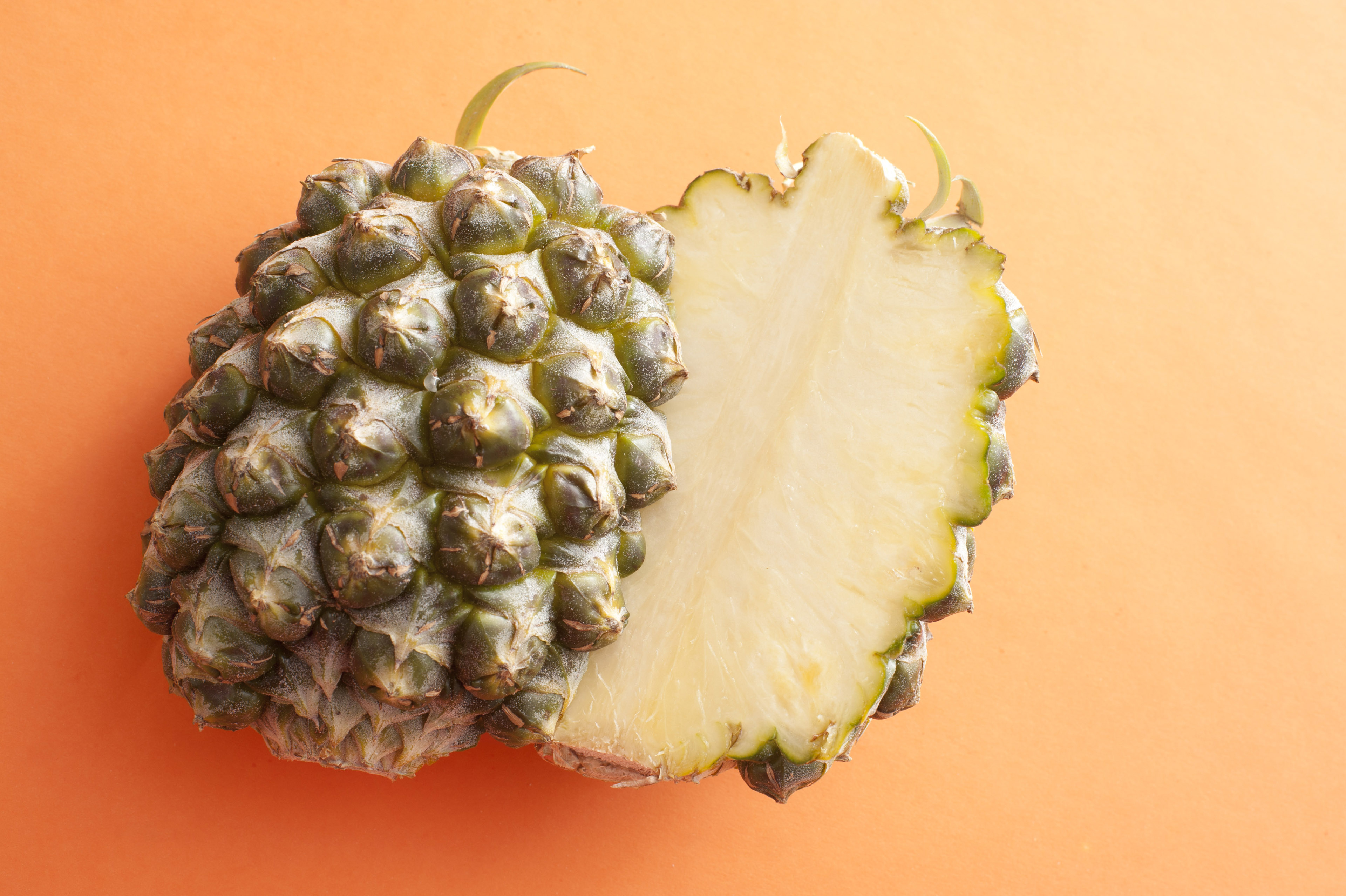 A fresh pineapple, sliced in half, isolated on a bright orange background.