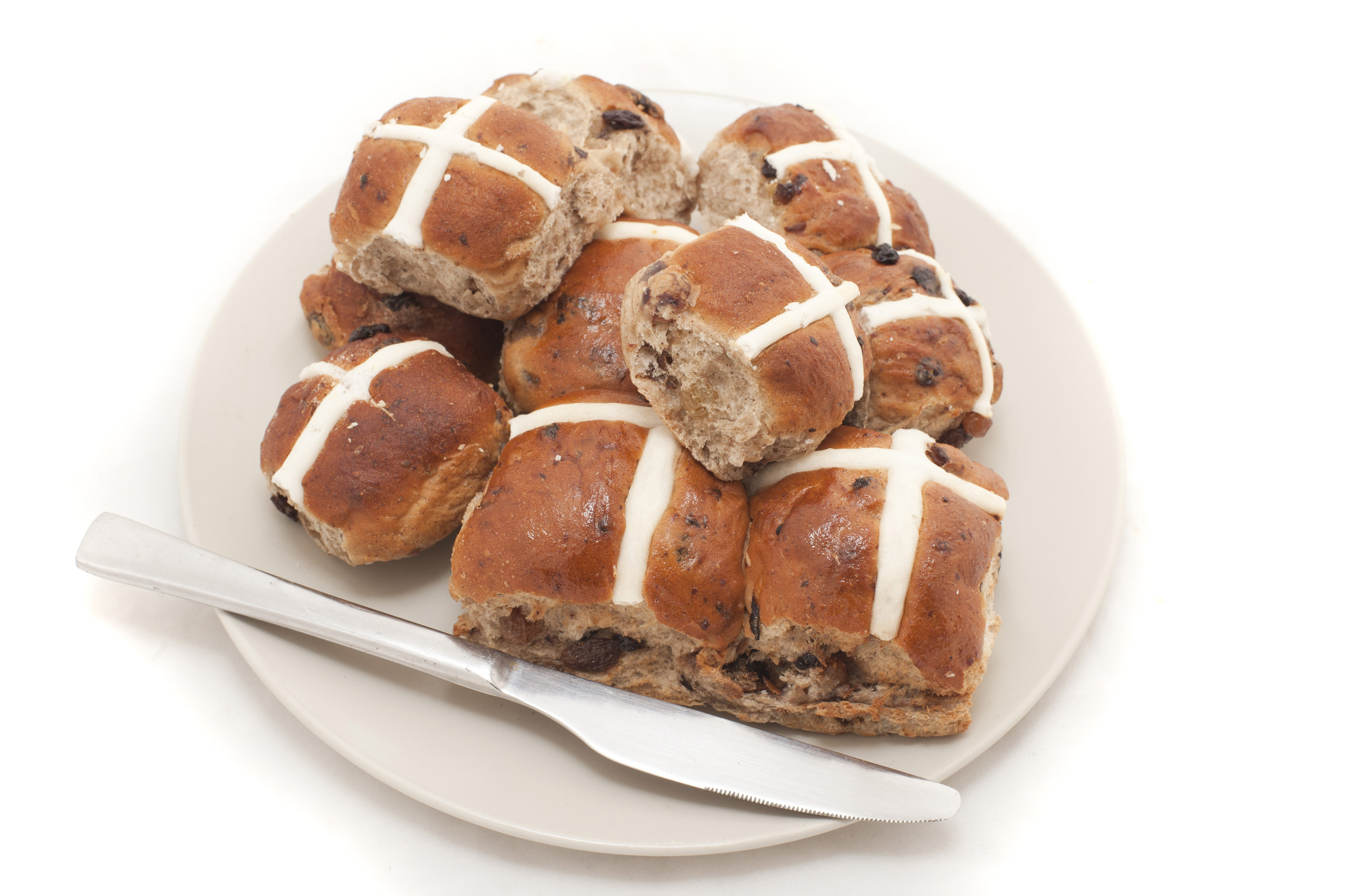 Still Life of Baked Hot Cross Buns Piled on White Plate with Silver Knife for Breakfast on White Background