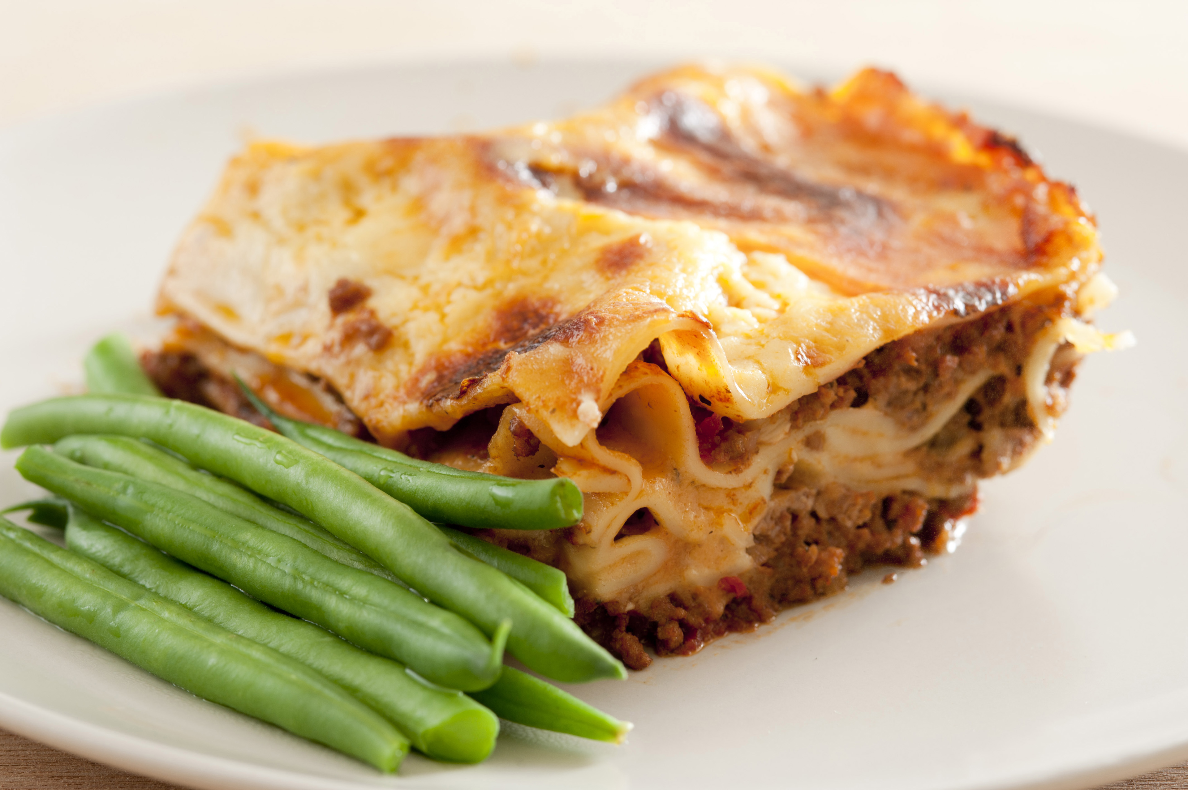 Serving of succulent meaty Italian lasagne pasta with green fresh beans, closeup view