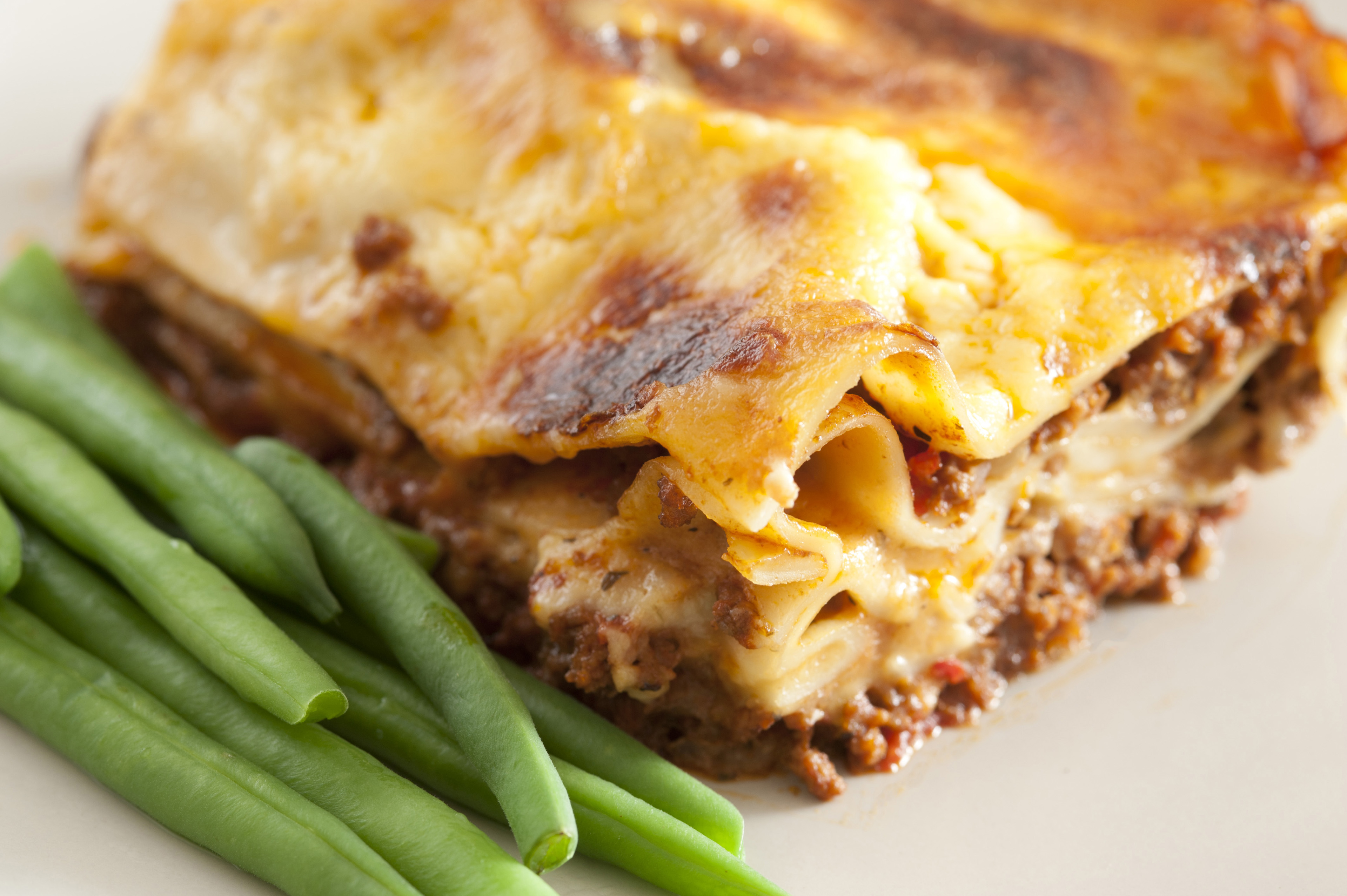 Close Up of Meal of Baked Lasagna Served with Green Beans on Plate for Dinner