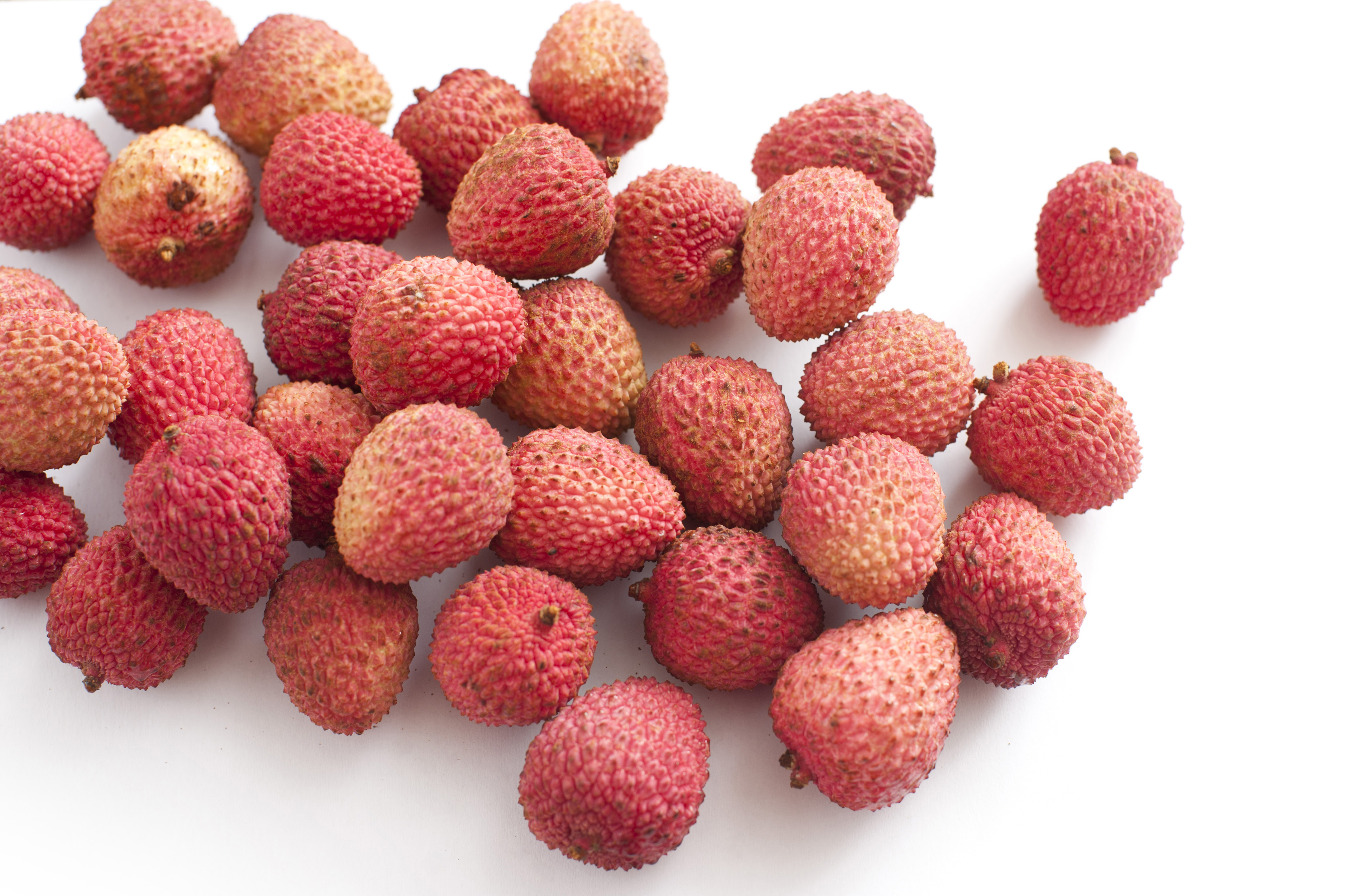 Assortment of Lychee Fruits in Pink and Red Rinds on White Background