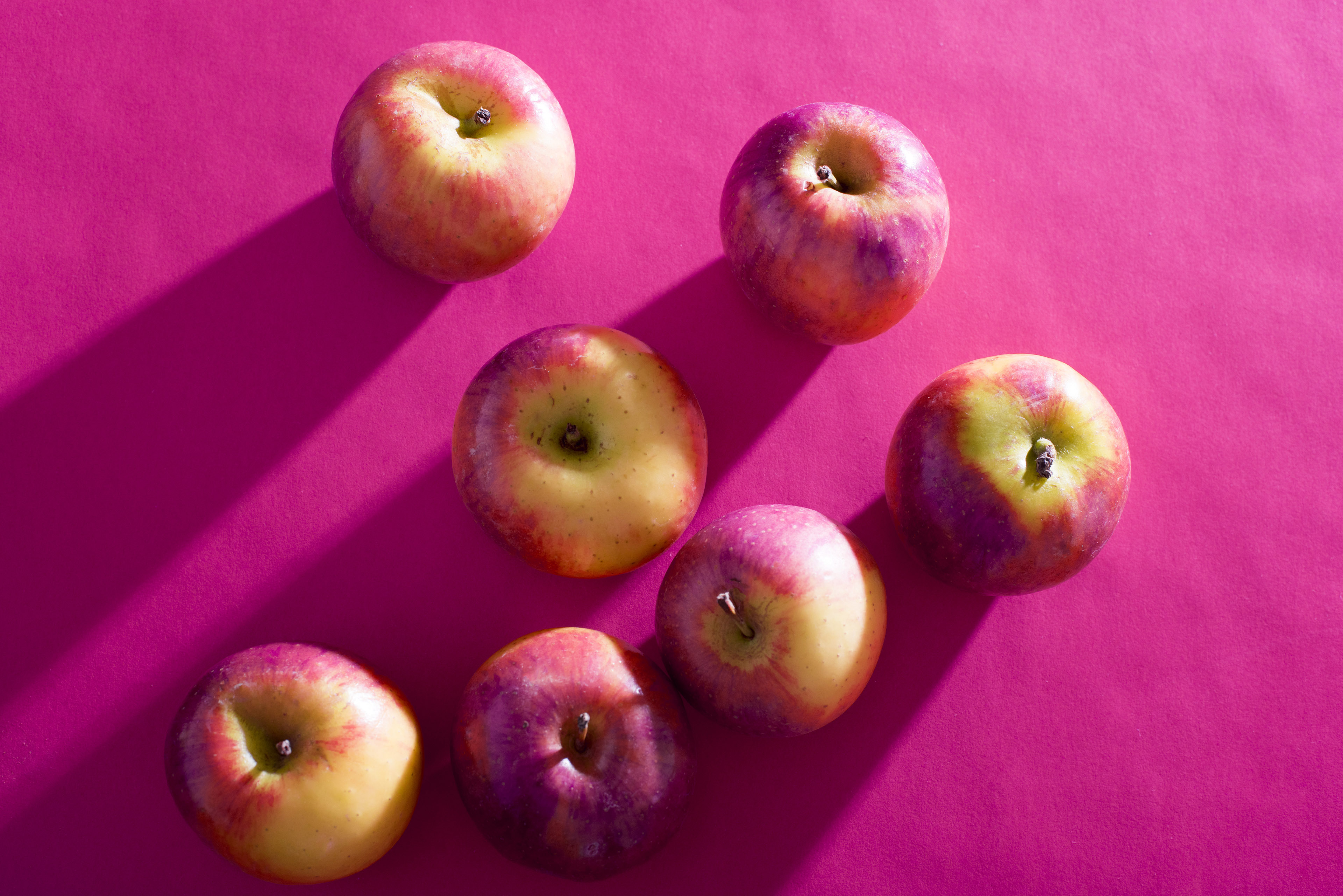 Seven fresh apples lying on purple background