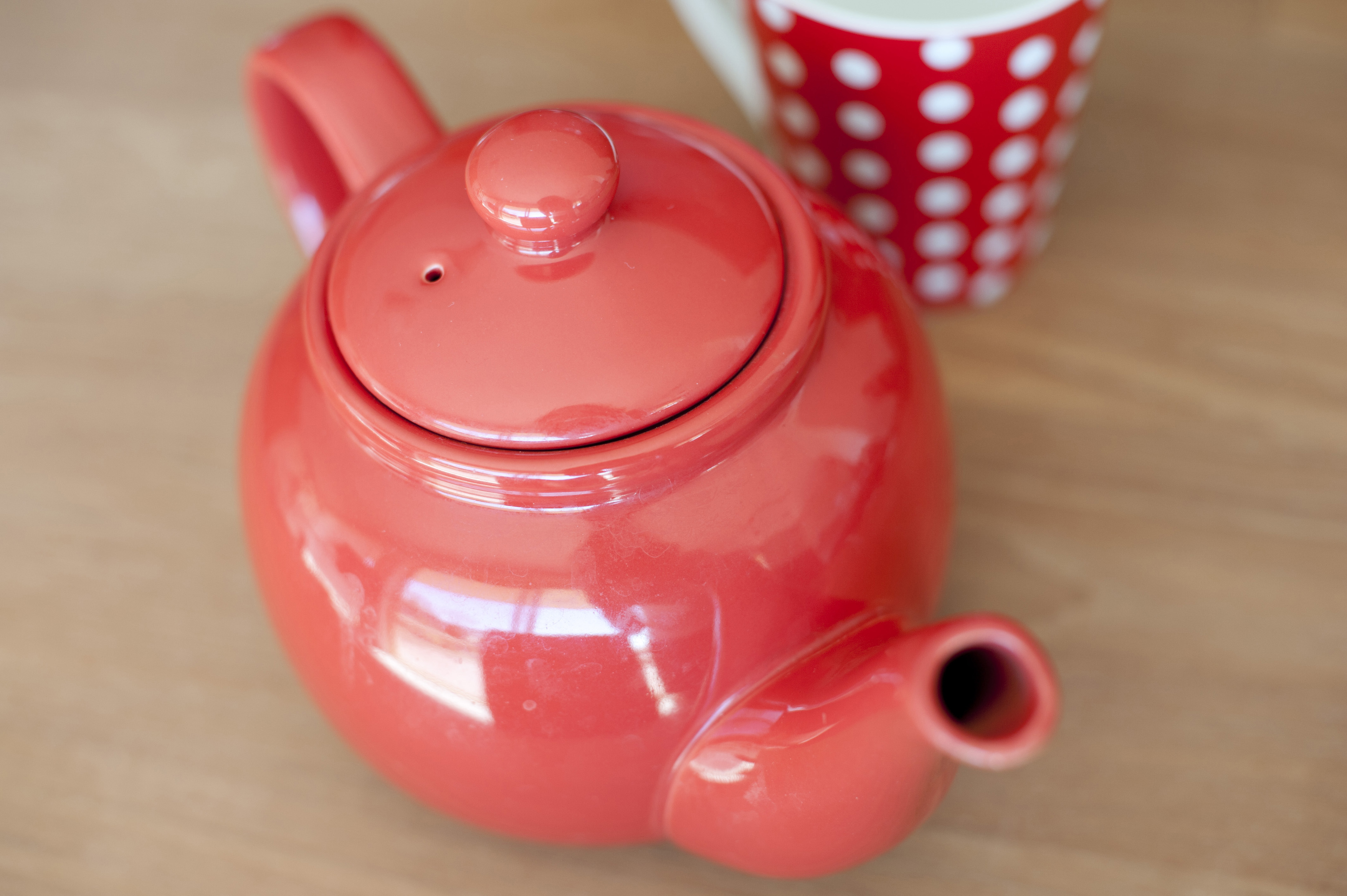 Close up Small Red Glossy Round Teapot on Top of Wooden Table