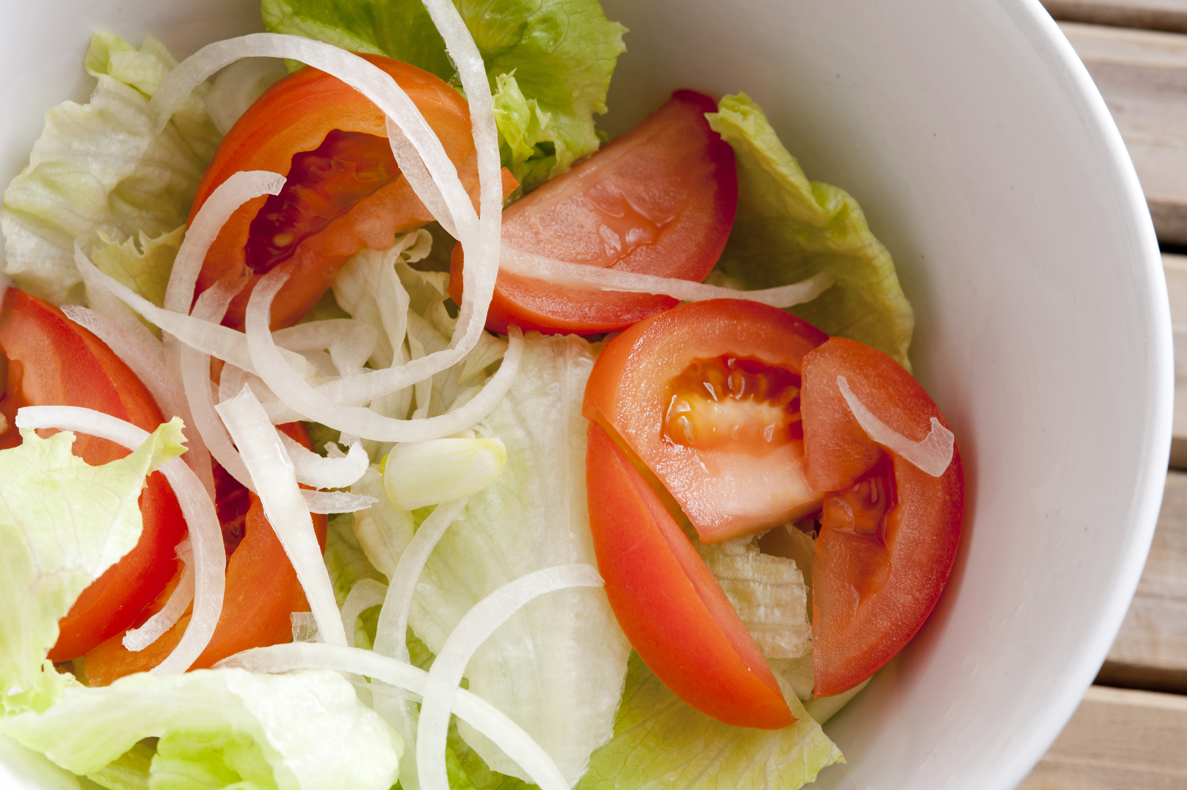 Close up Fresh Vegetable Salad on White Bowl with Cabbage, Lettuce and Tomatoes