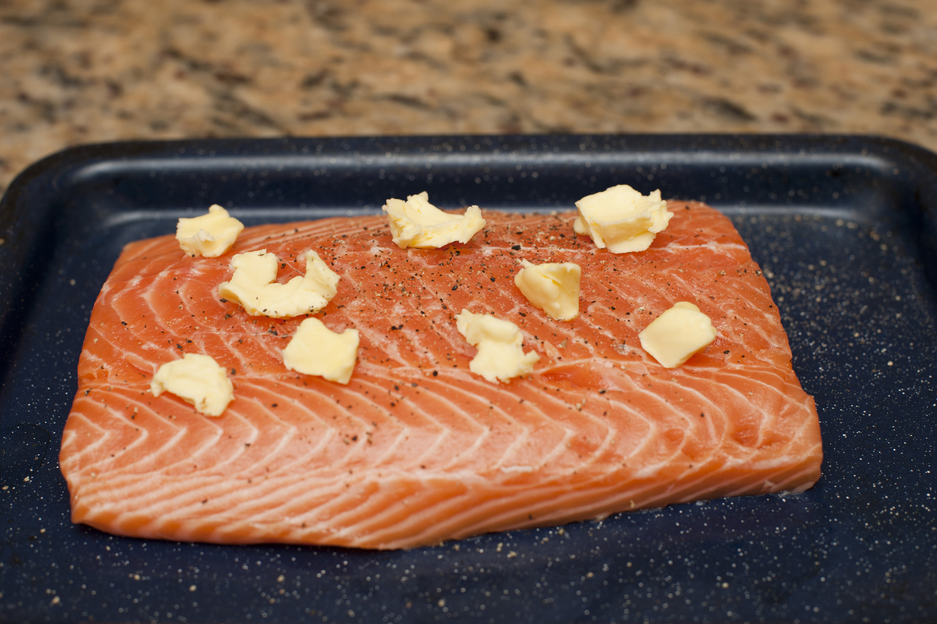 Raw Filet of Salmon Seasoned with Pepper and Pats of Butter on Baking Pan on Counter Top