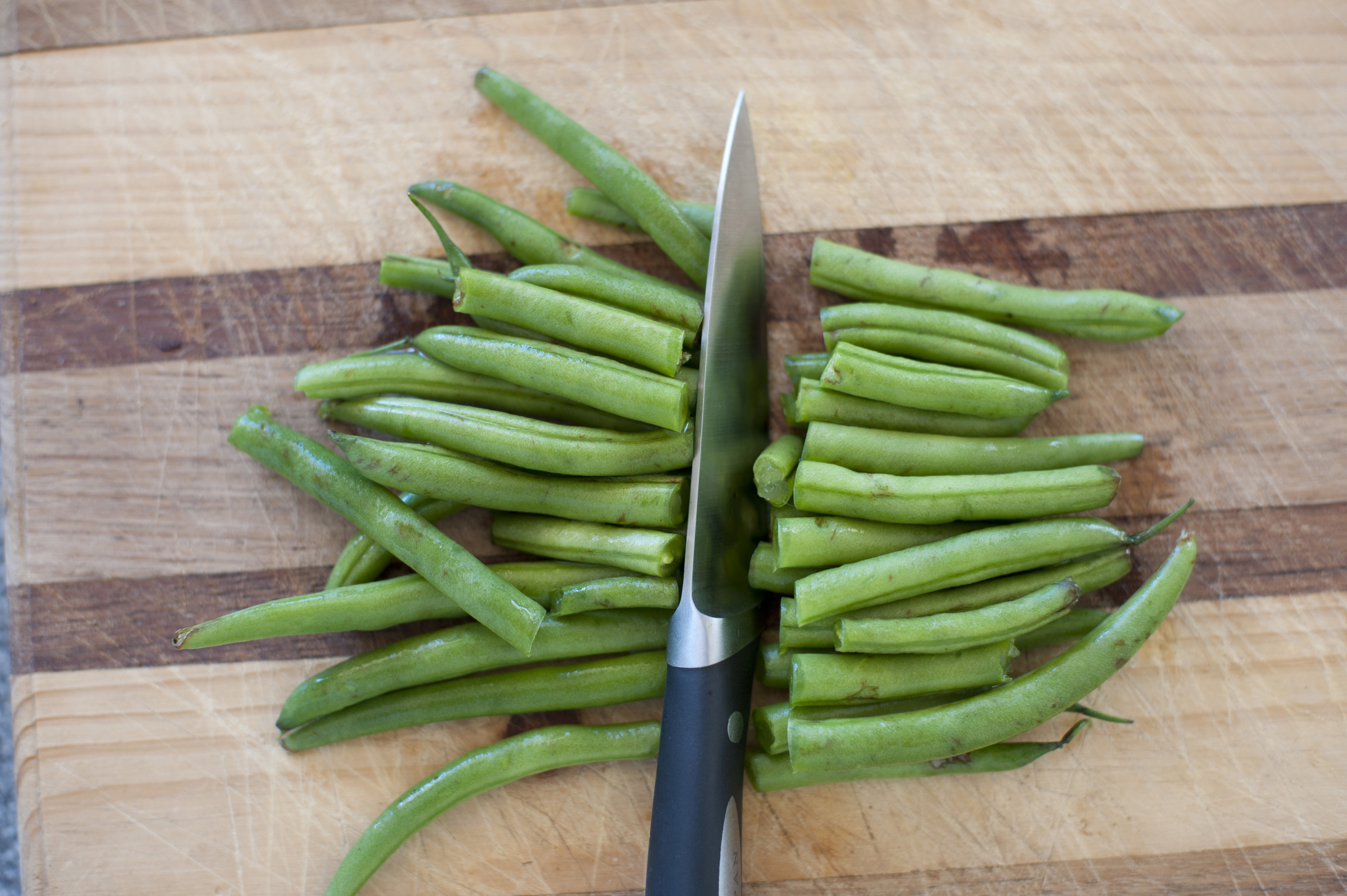 Close up Slicing Healthy Fresh Green Beans using Knife on Top of Wooden Chopping Board