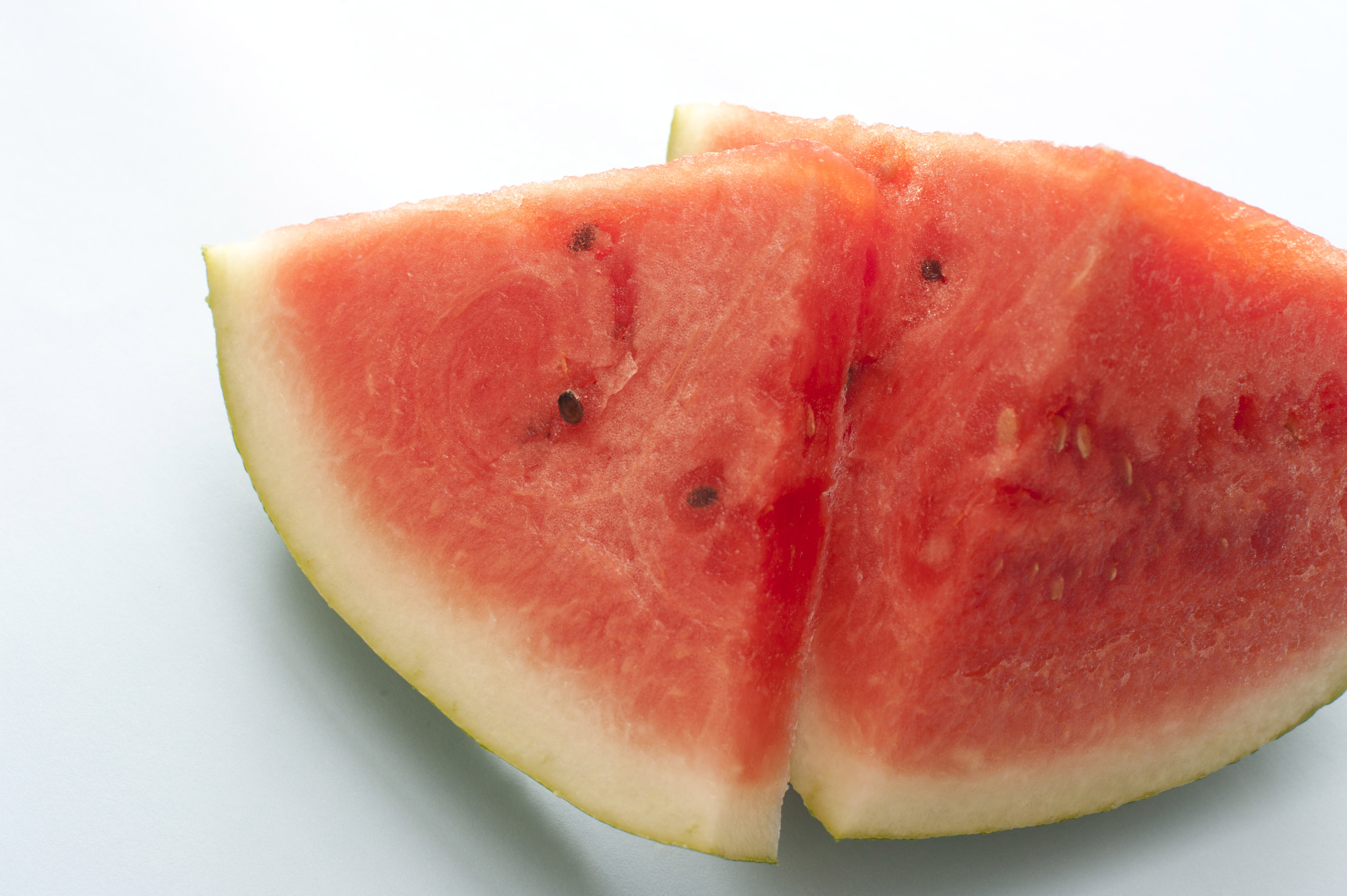 A sliced and quartered fresh, juicy watermelon isolated on a white background with copy space.