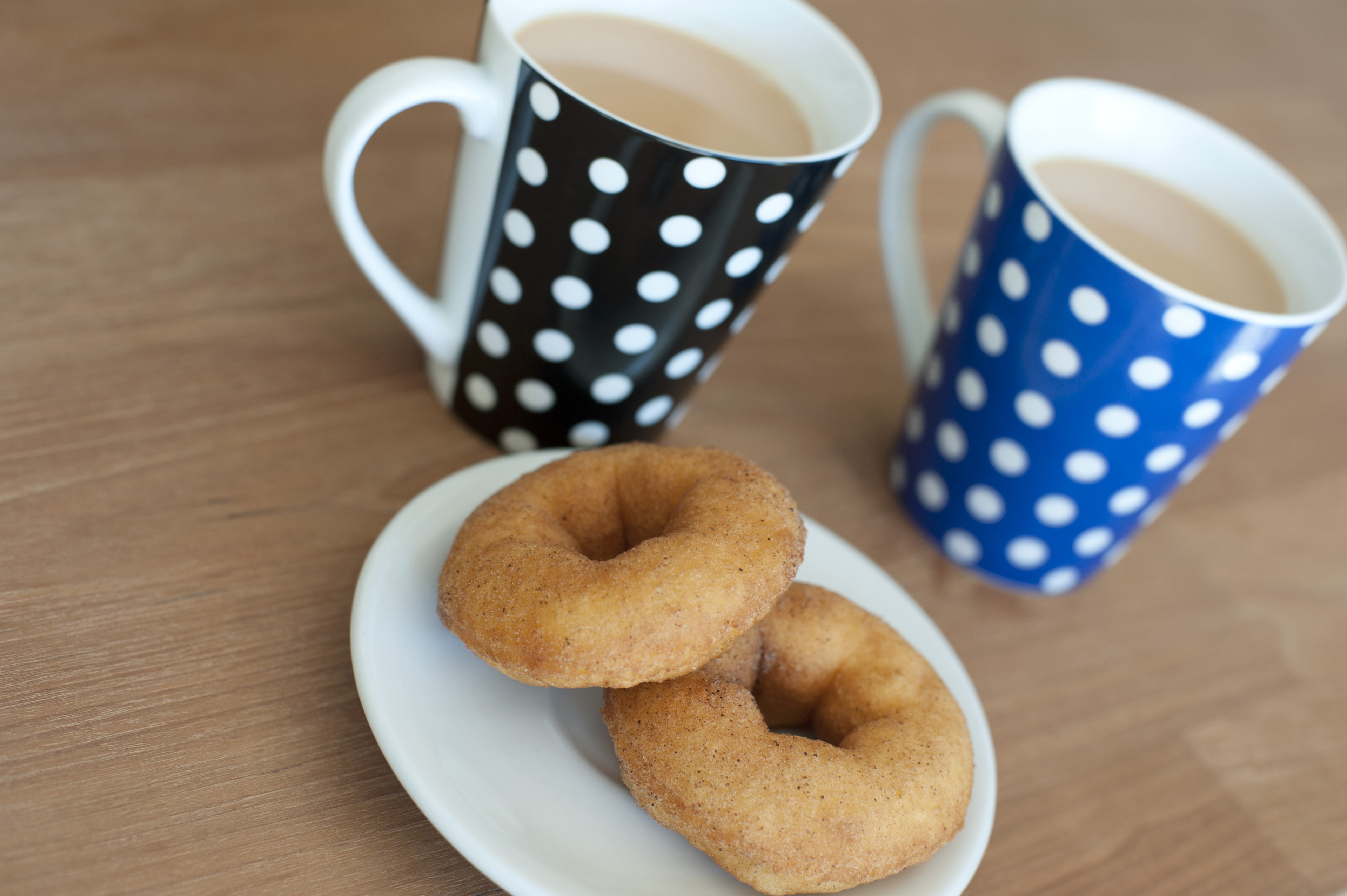 Close up Cups of Tea and Sweet Doughnuts on Plate Served on Top of Wooden Table