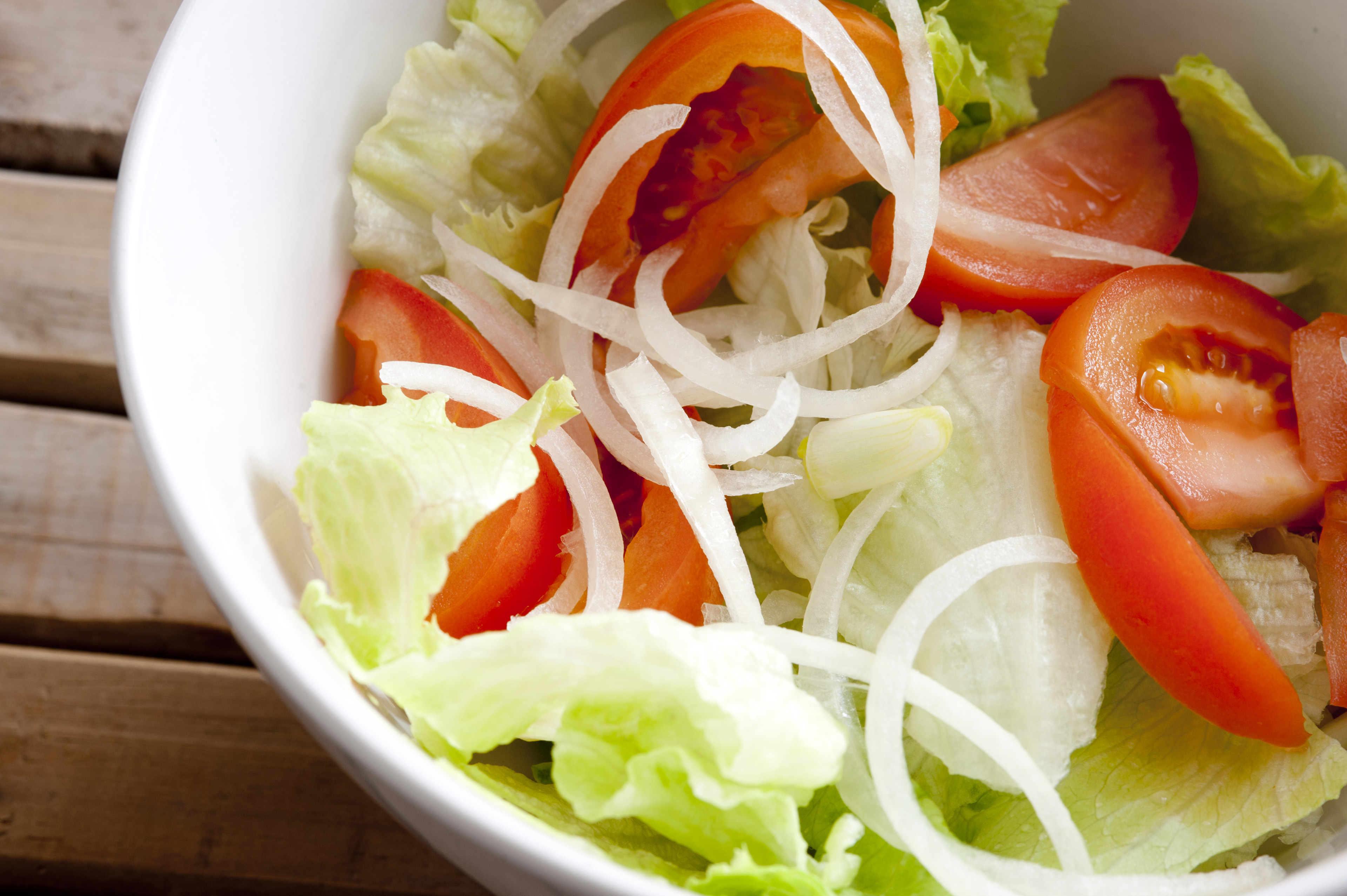 Freshly healthy mixed salad with juicy tomatoes, lettuce and onion tossed in a bowl, high angle view