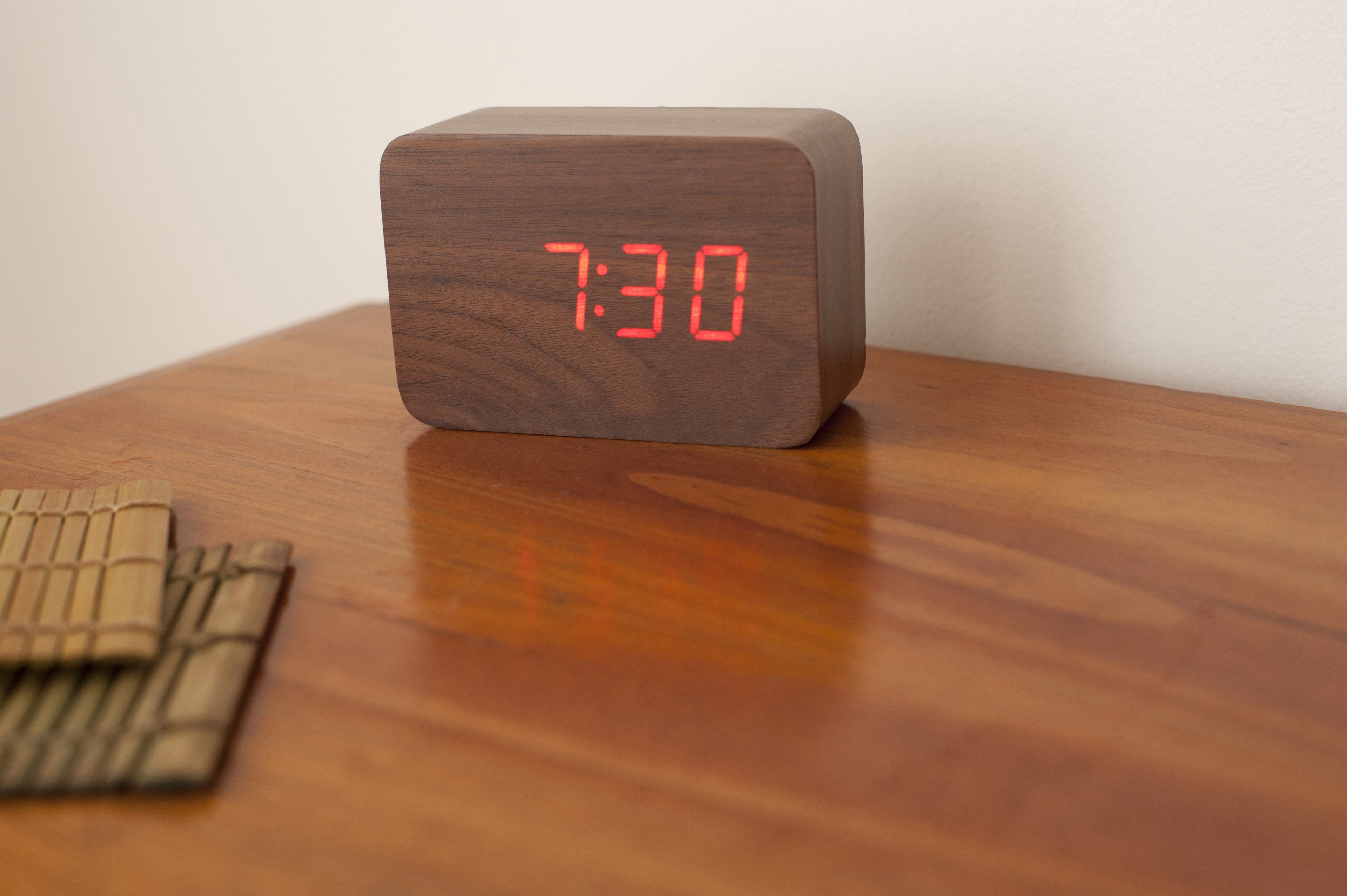 Alarm clock showing half past seven on a wooden table with copyspace