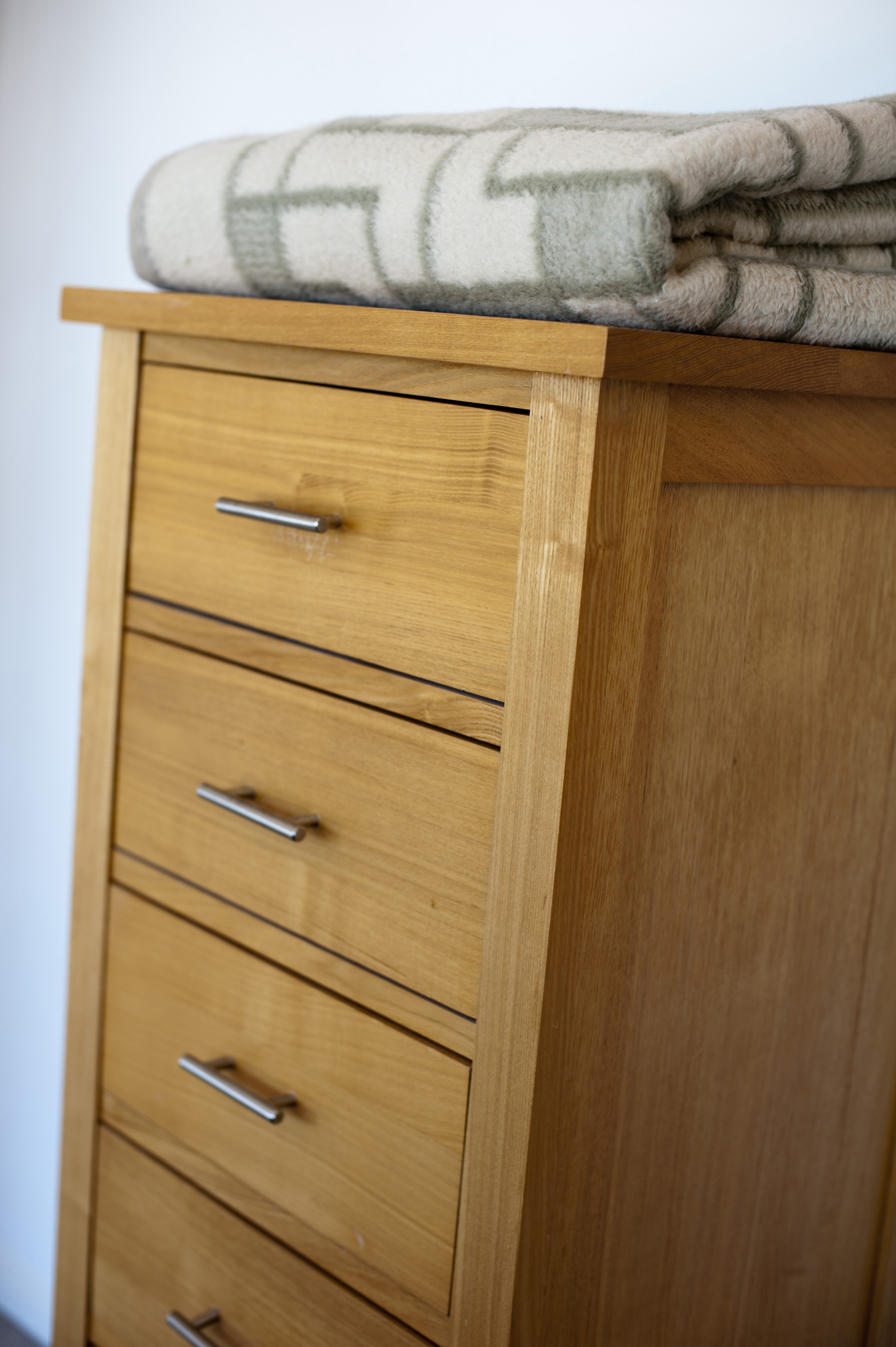 Small natural wood chest of drawers with a folded blanket on top against a white wall