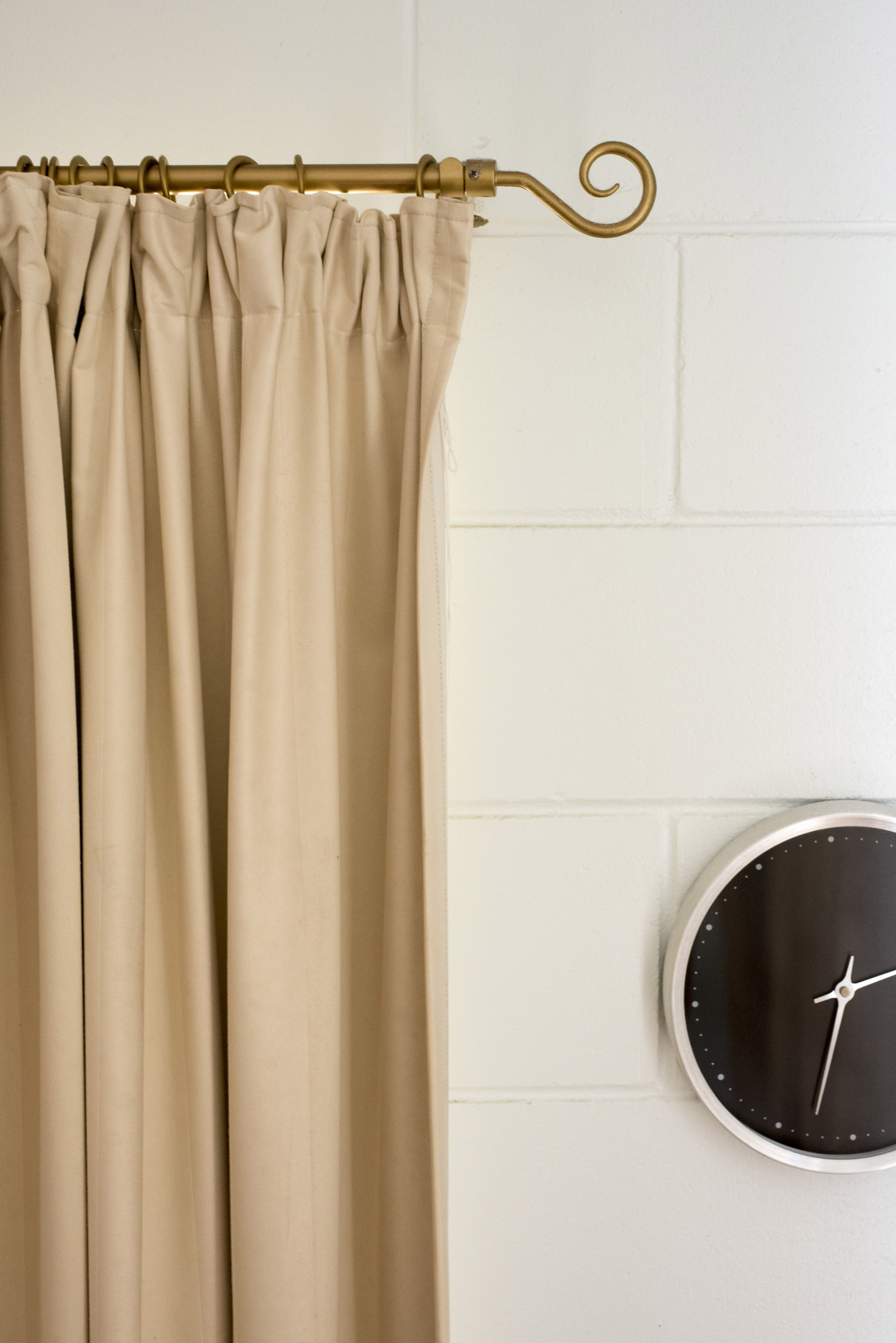 An Abstract Home Decor With Beige Curtain Rod And Black Clock Hanging On A White