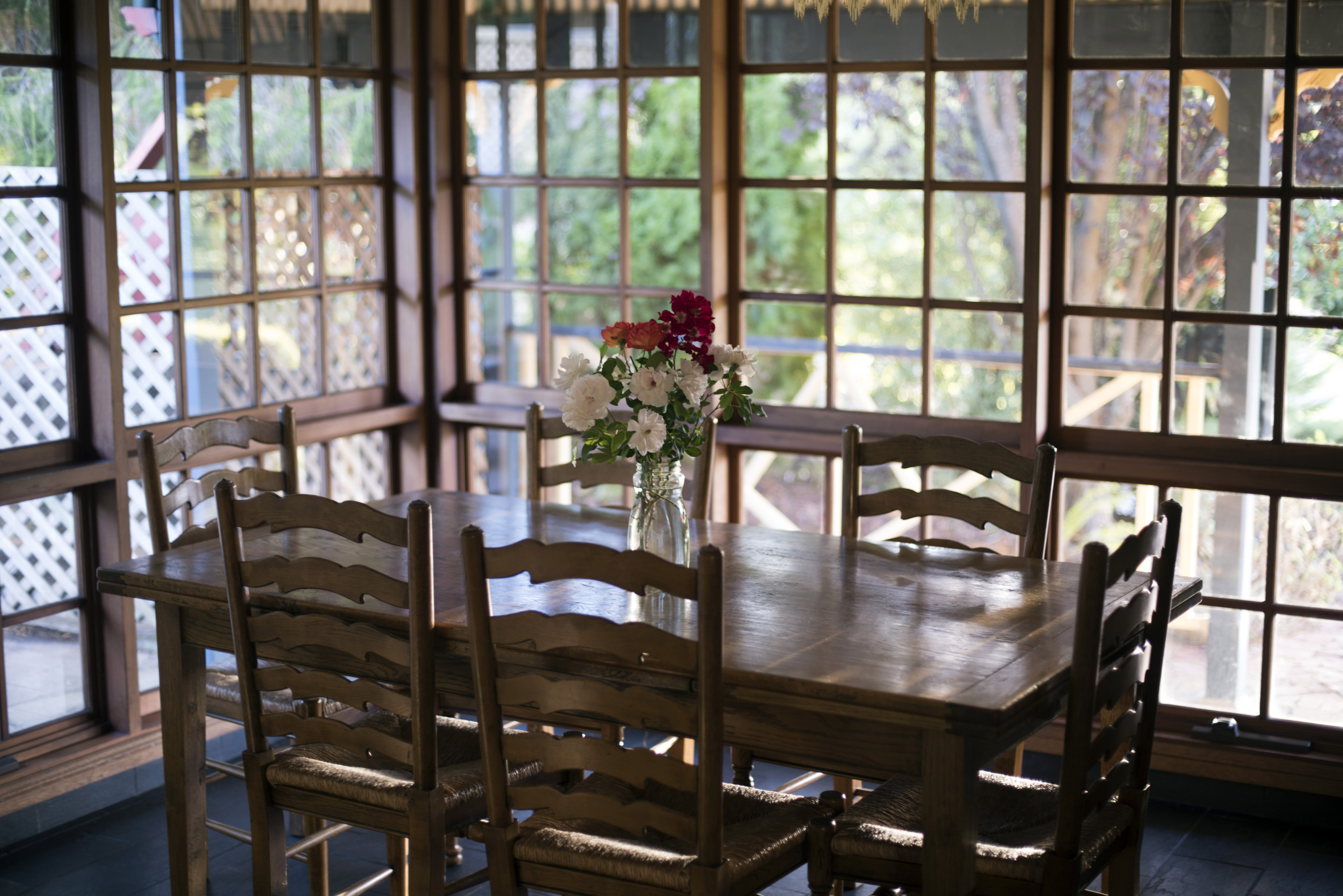 An empty, vintage timber dining room with wide windows, table and a vase of fresh flowers.