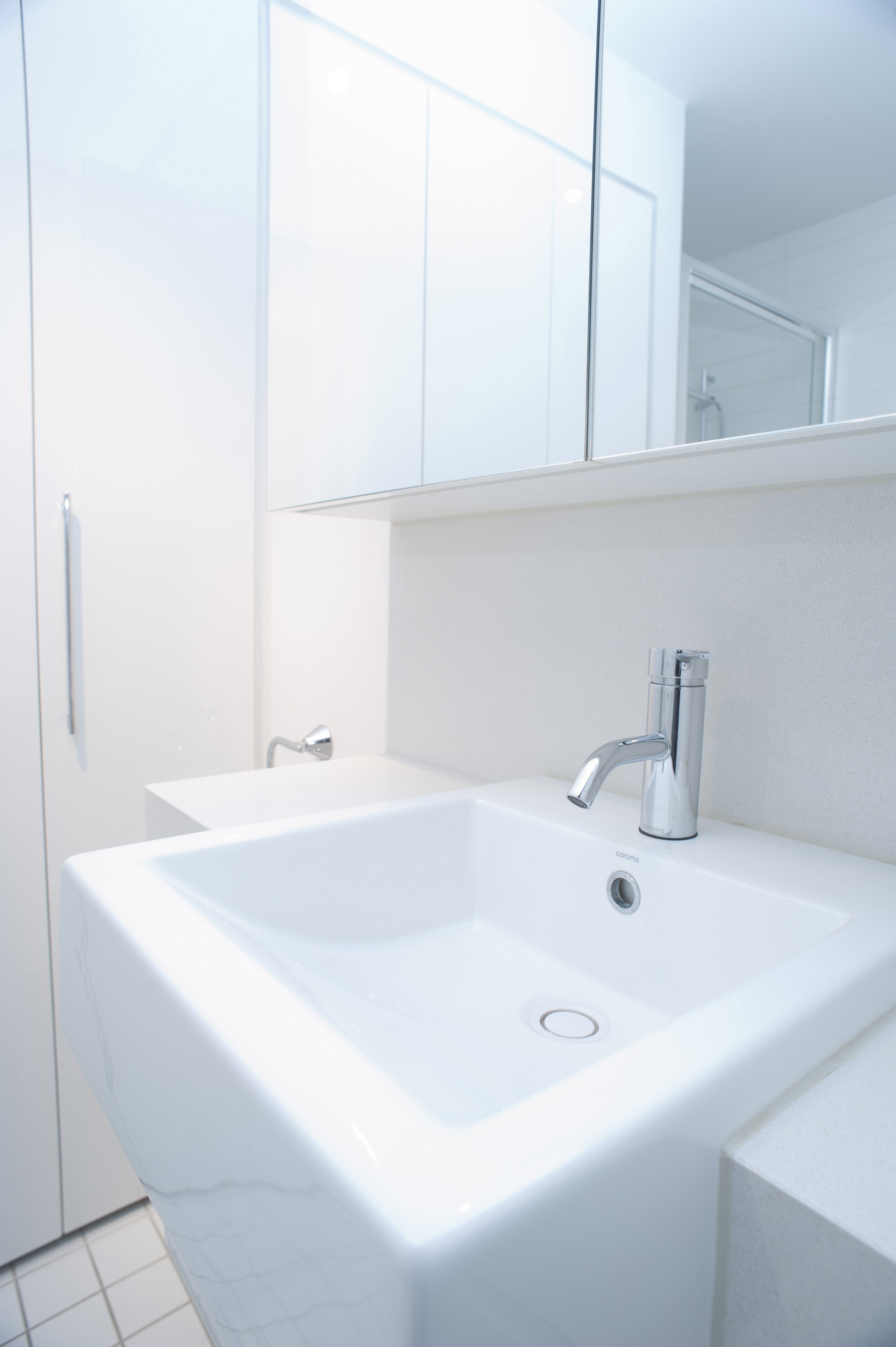 Modern rectangular white hand basin with a mixer tap in a white bathroom interior with mirror and cabinets