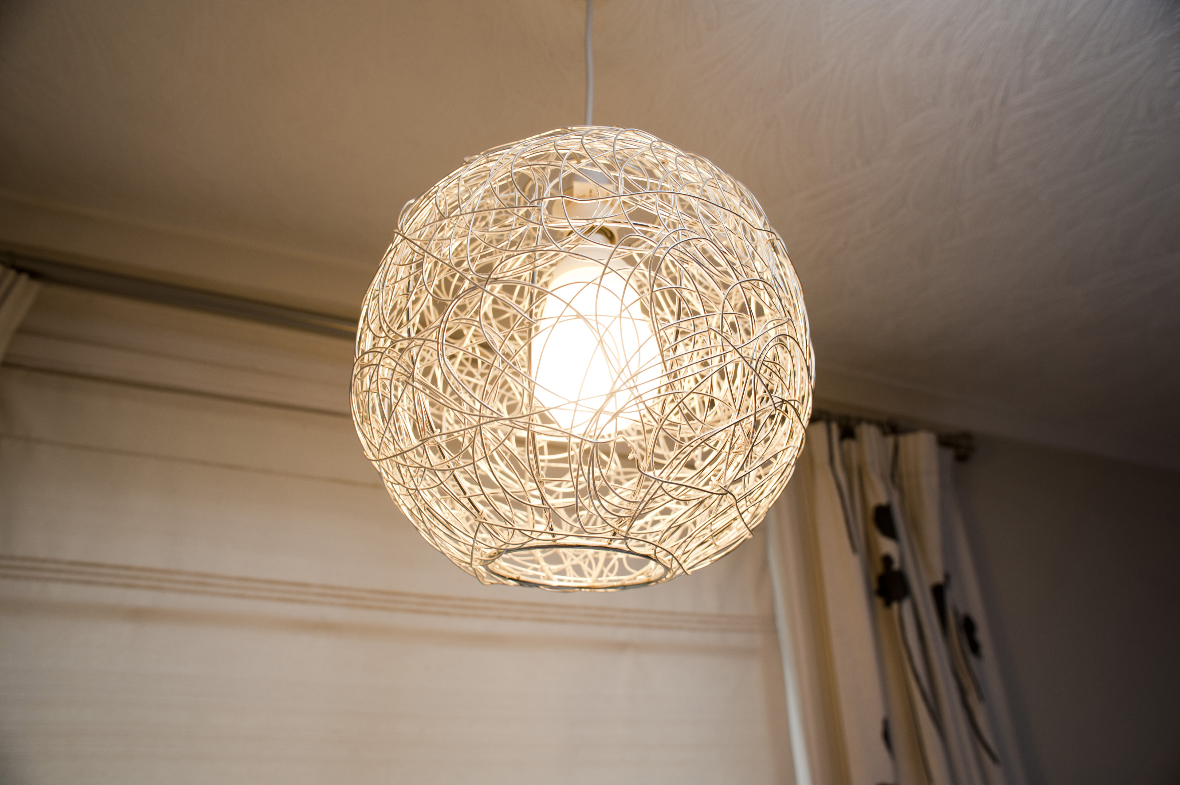 Hand crafted spherical rattan or wicker globe lampshade with an illuminated light bulb hanging from a ceiling indoors