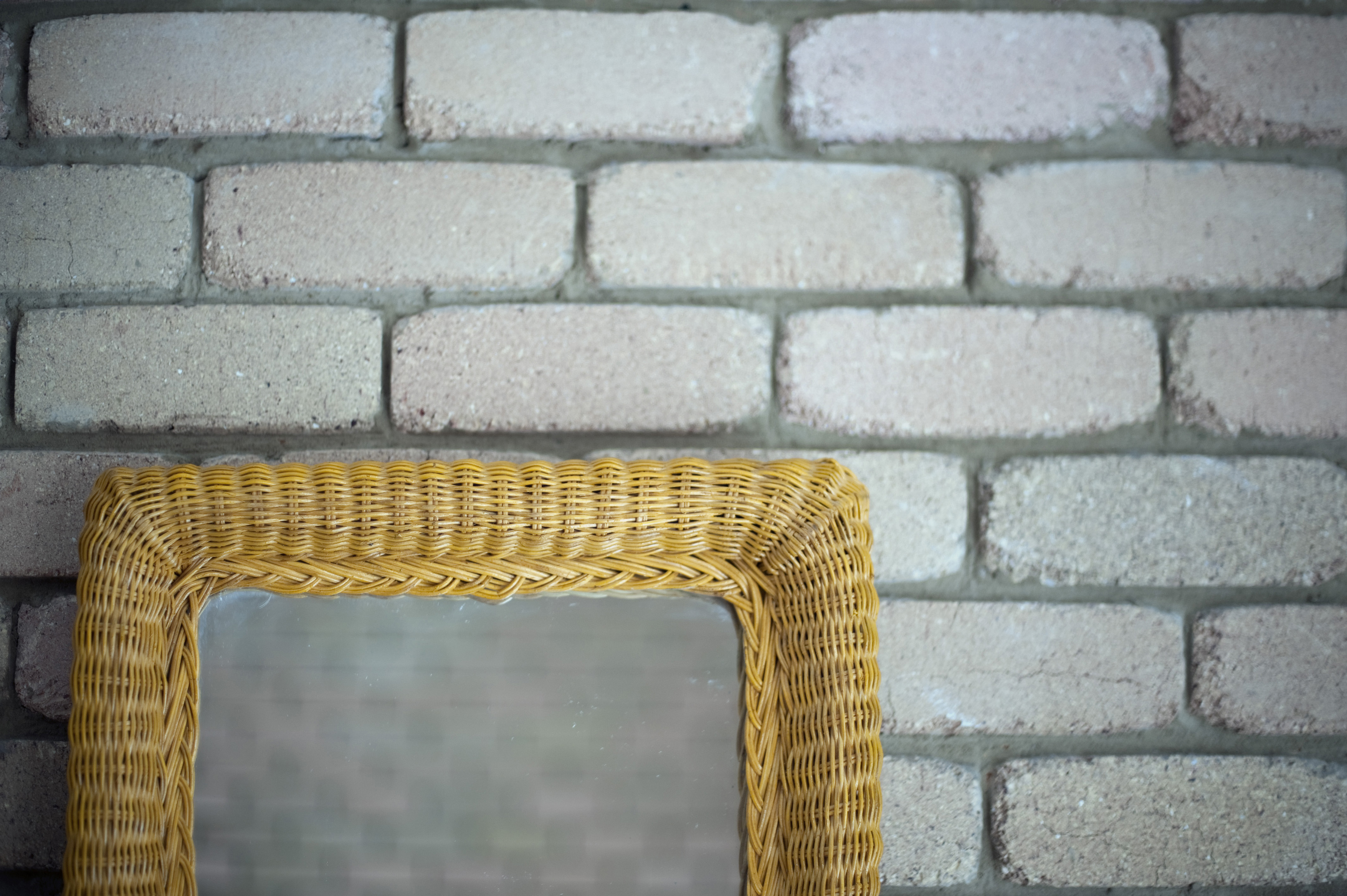 Rattan or wicker framed mirror standing against a rustic white painted brick wall reflecting the brickwork