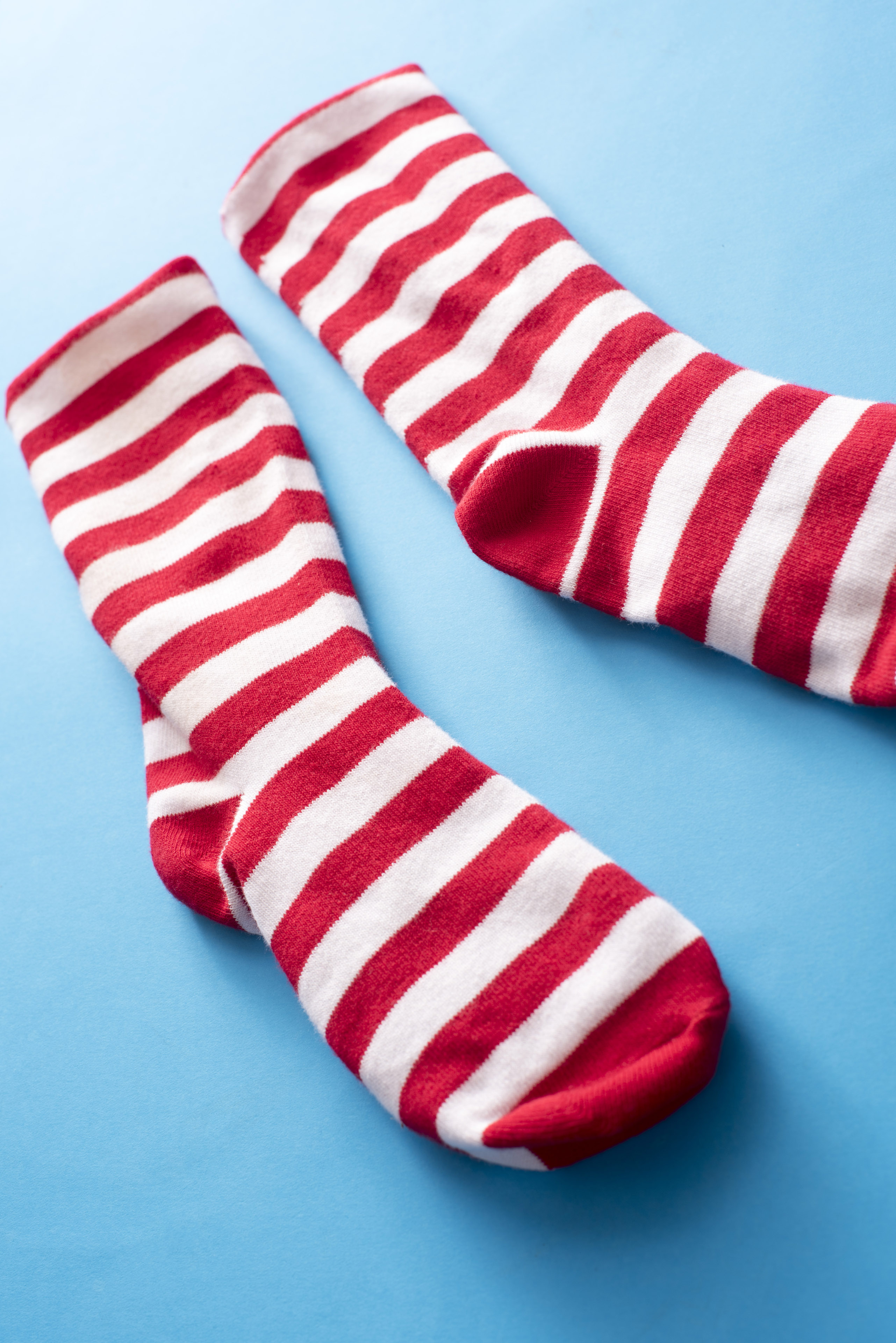 A pair of red and white striped Christmas Santa socks isolated on a plain blue background.