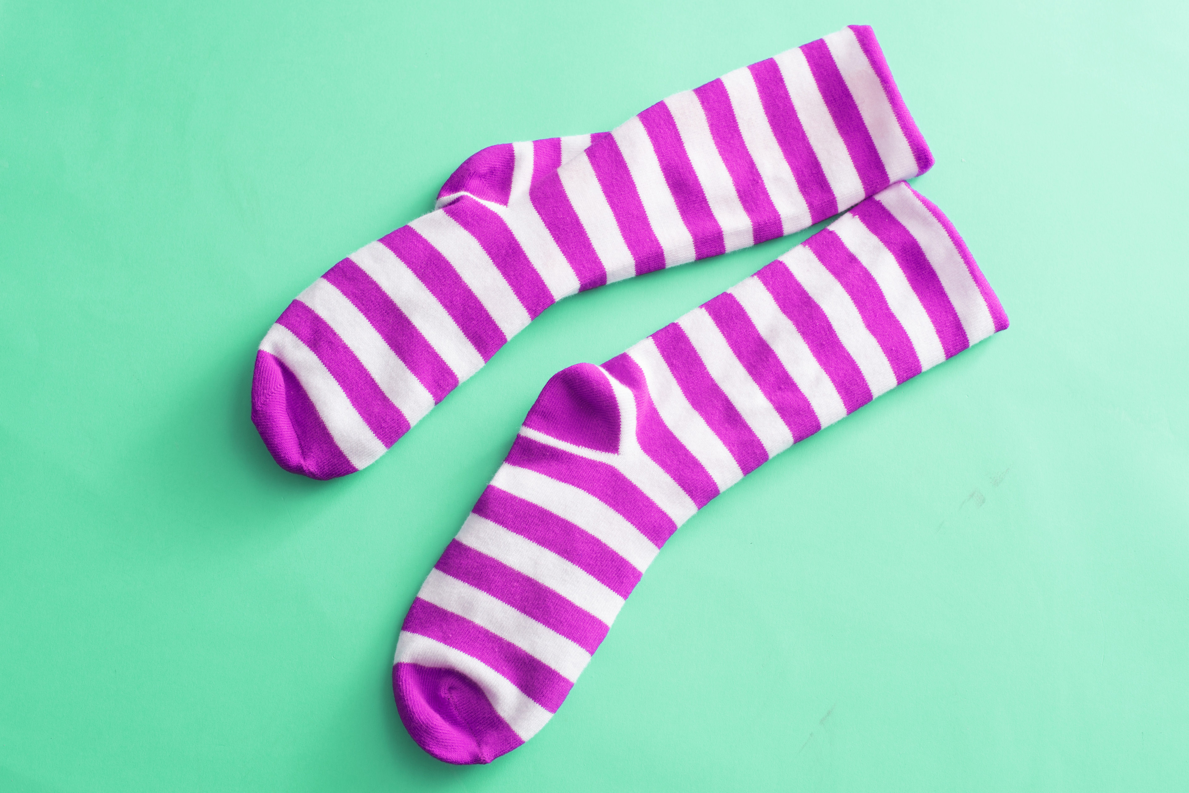 Colorful pair of bright striped magenta pink socks over a green background with copy space