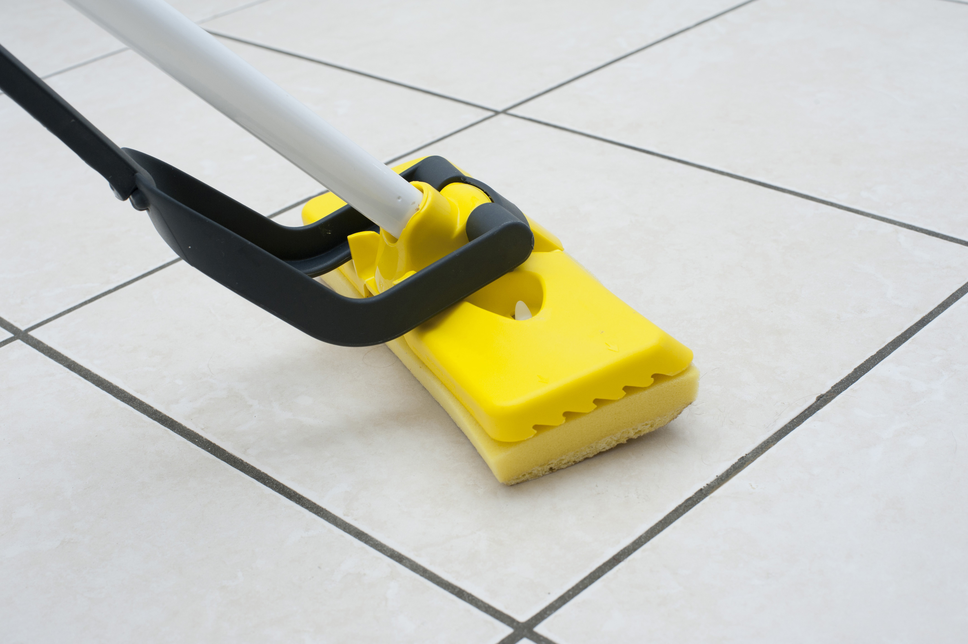 Mopping the white tiled kitchen or bathroom floor using a colorful yellow plastic squeegee in a household chores, cleanliness and hygiene concept