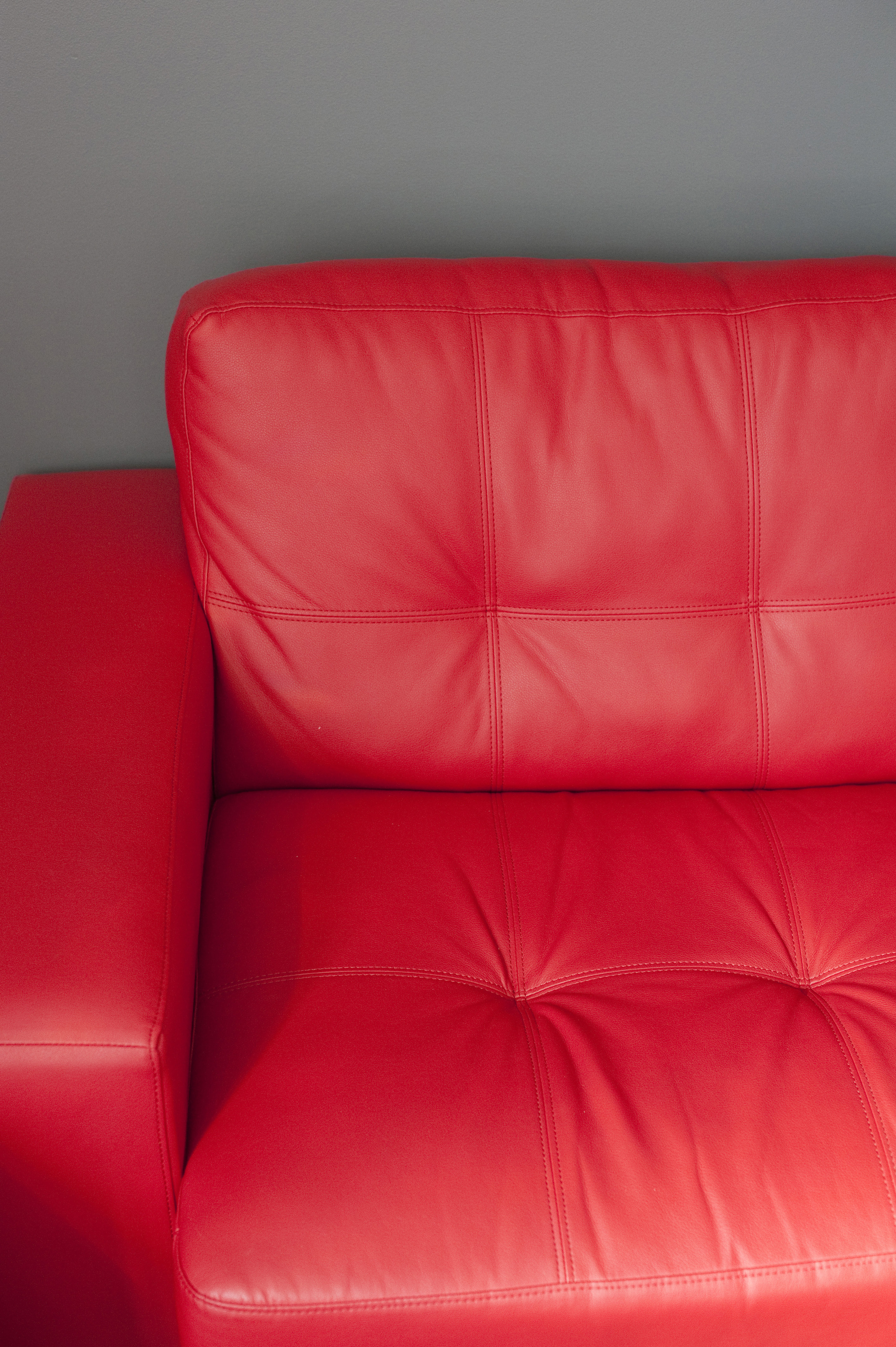 Arm and portion of a comfortable red leather upholstered settee on a grey wall, closeup detail