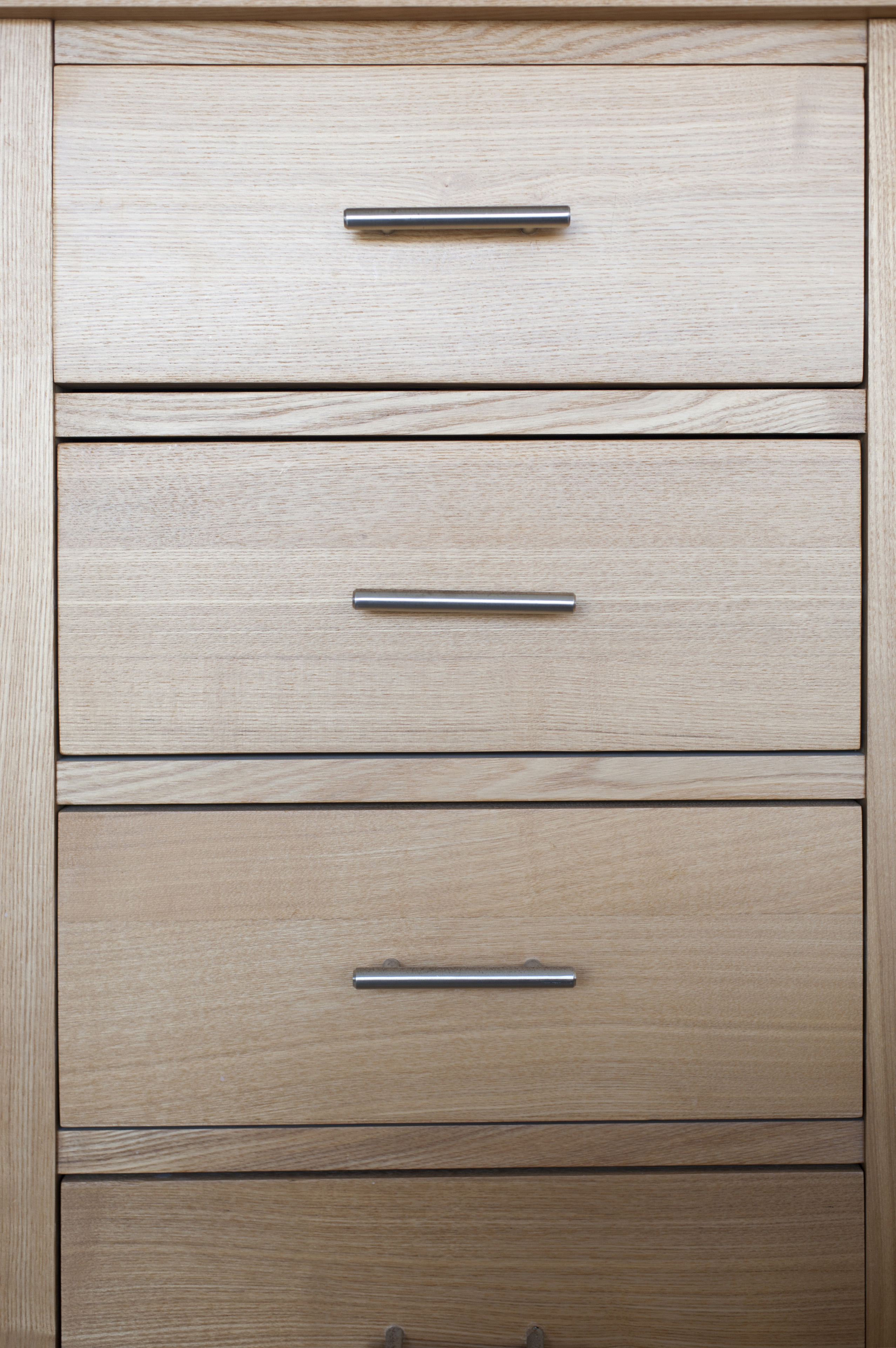 Close up full frame view of a small natural wood chest of drawers for household storage