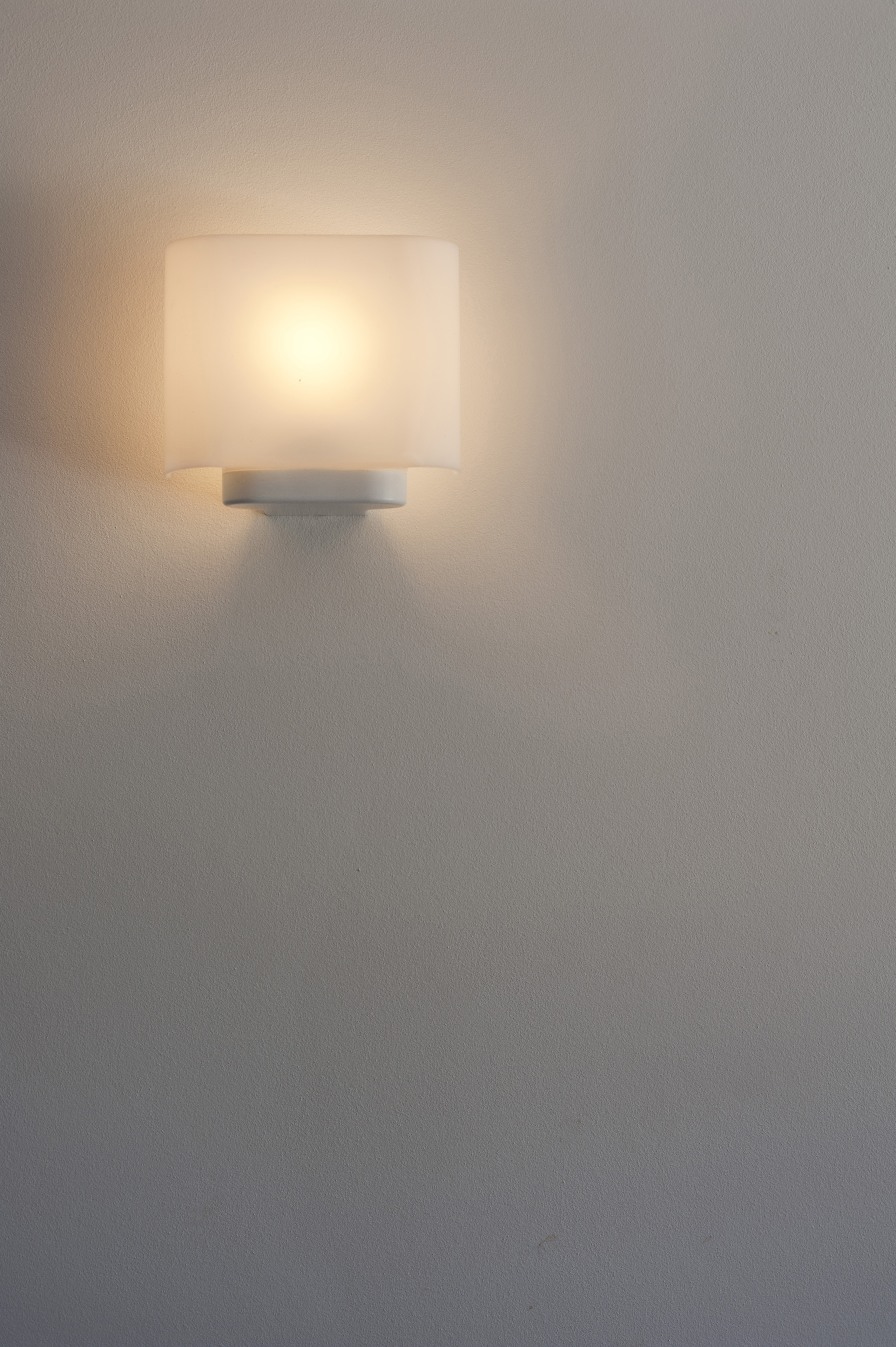 Single illuminated glowing wall sconce or wall light with a lampshade on a grey wall with copyspace