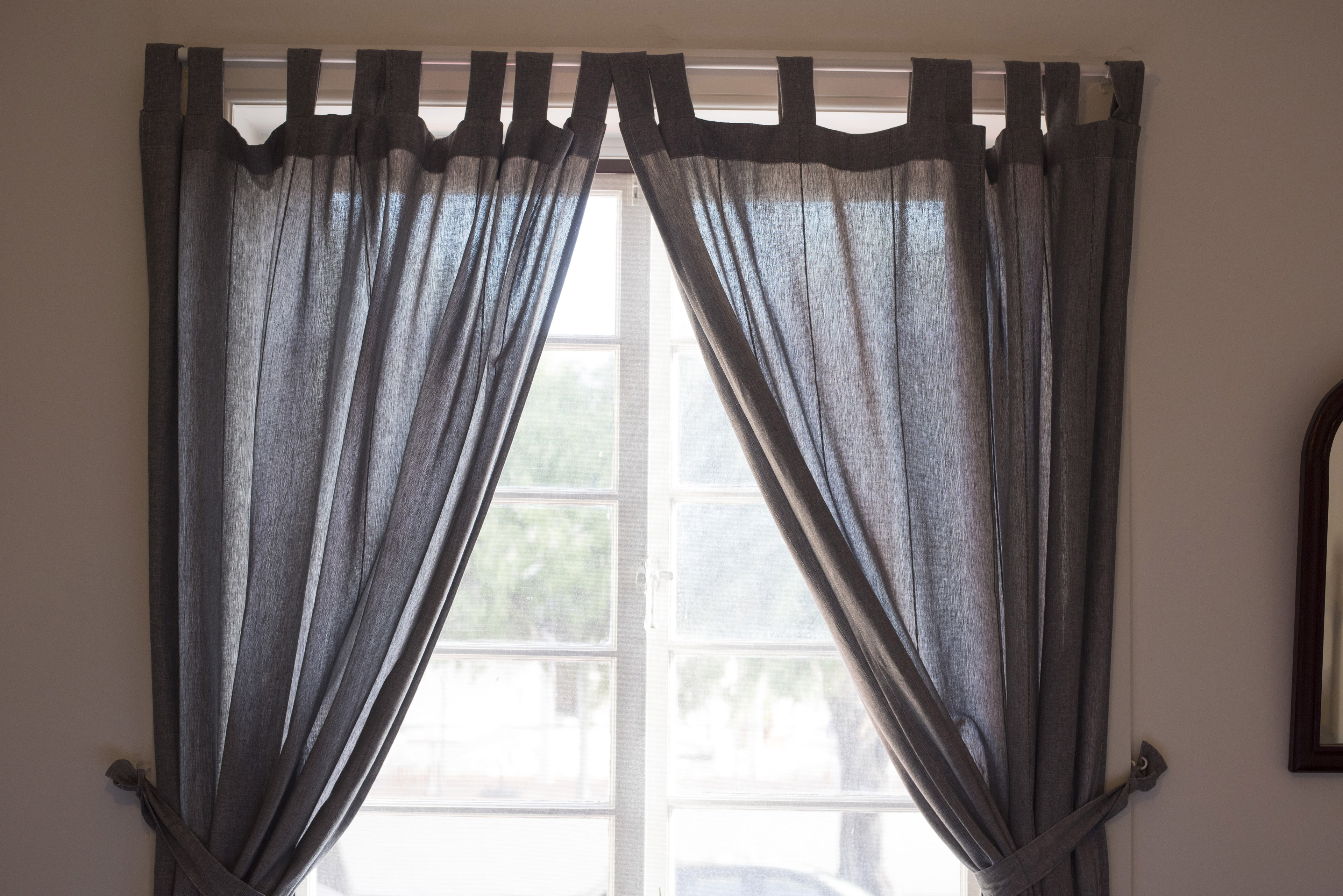 Window in a home with dark colored drapes or curtains hanging on a simple rod pulled to the sides with ties in a translucent fabric