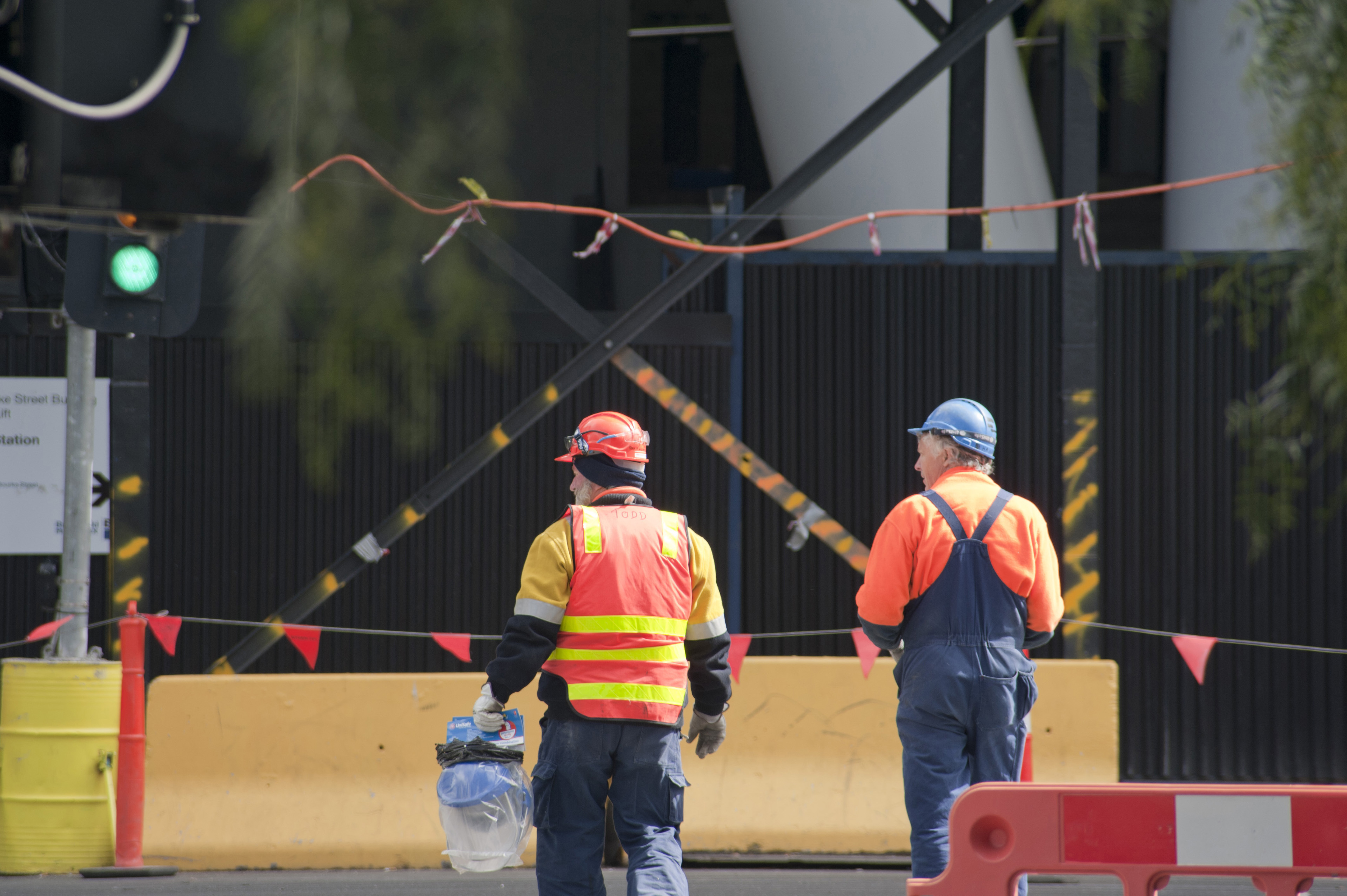 Two construction workers on a road crew standing on a building site with their backs to the camera watching for traffic with a green light in the background