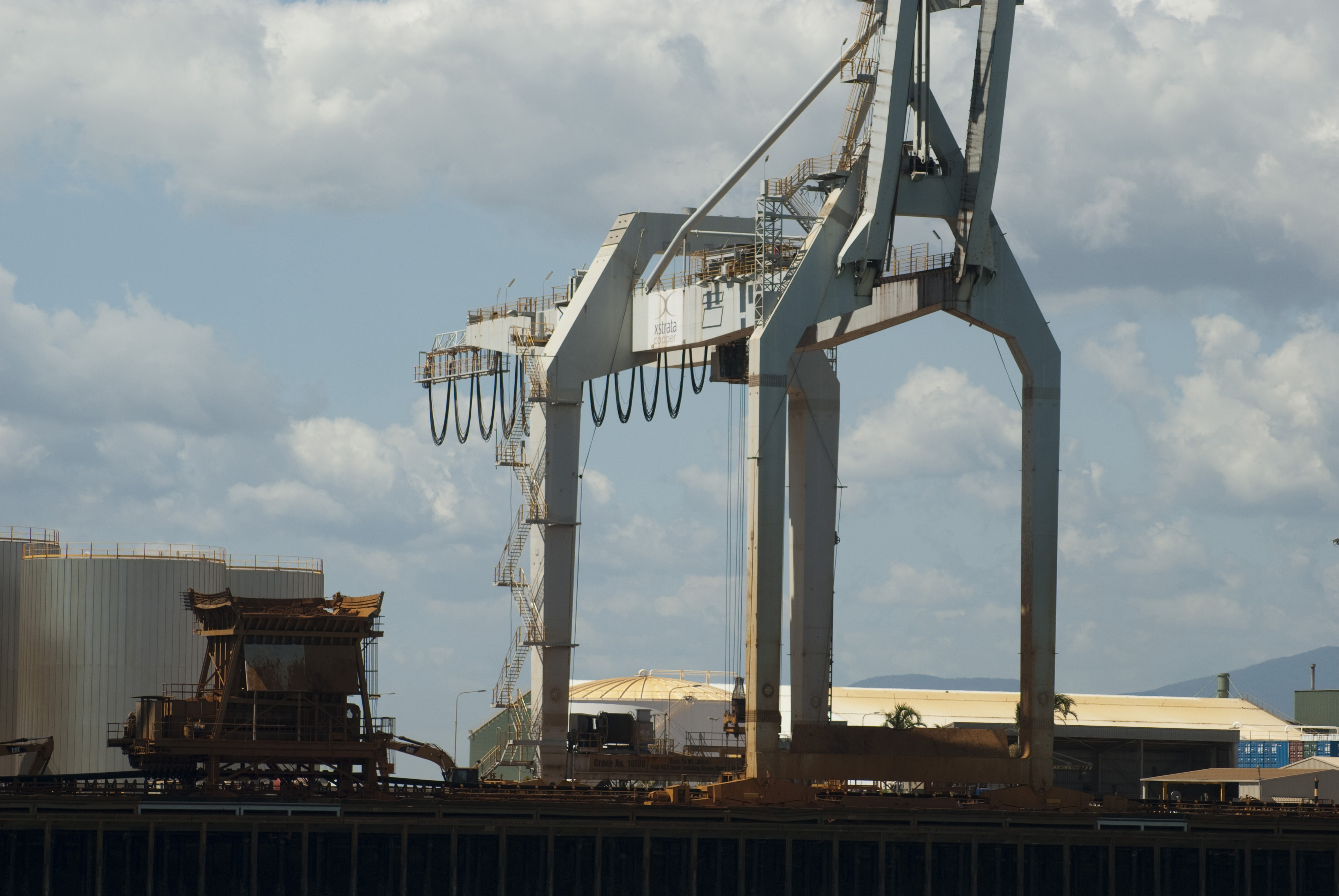 Industrial cranes at a cargo depot standing on the wharf ready for loading cargo onto ships at a port or harbor