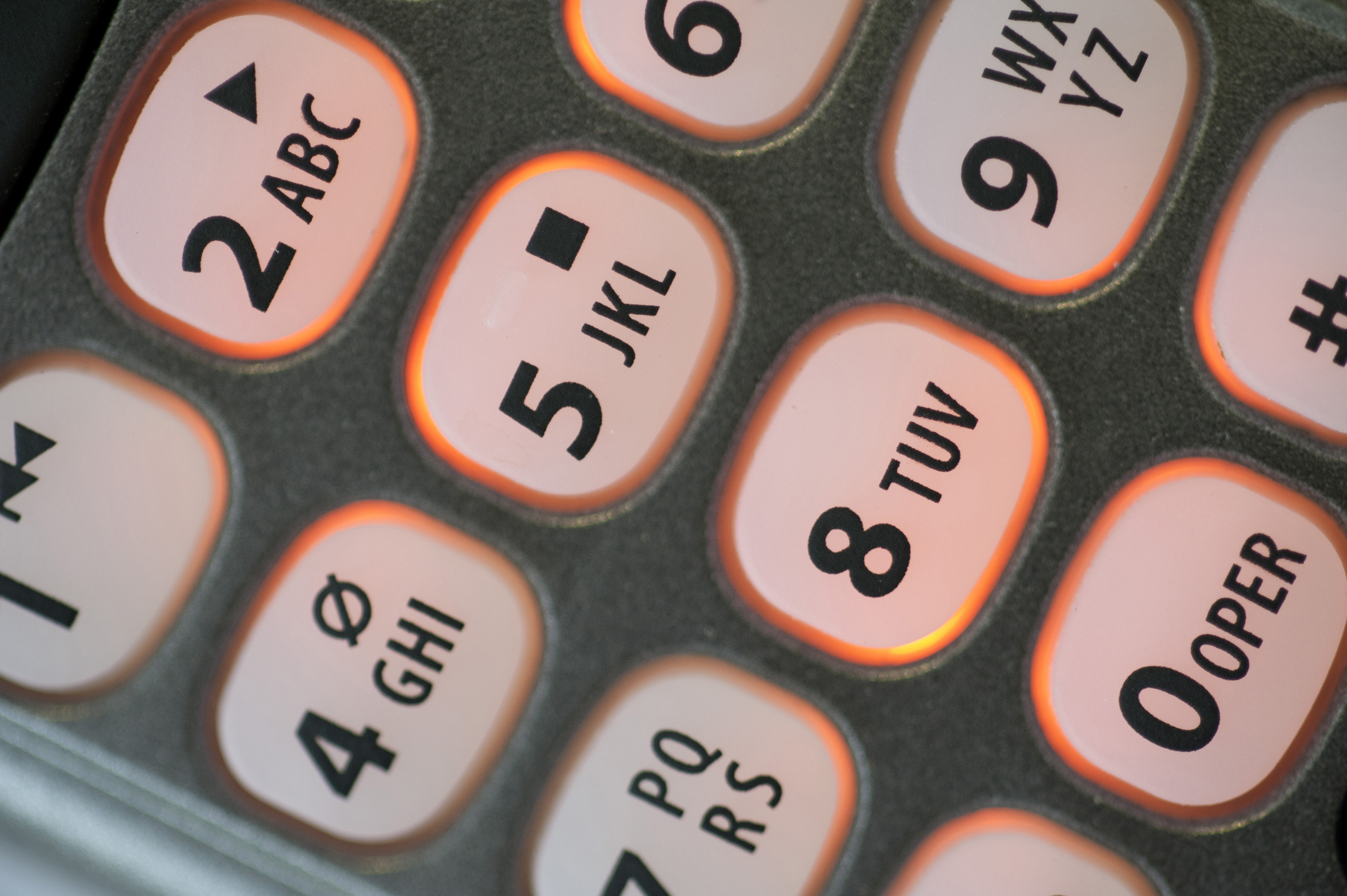 Keys and keypad on a telephone handset with numbers and alphabet letters in a communications concept, close up view