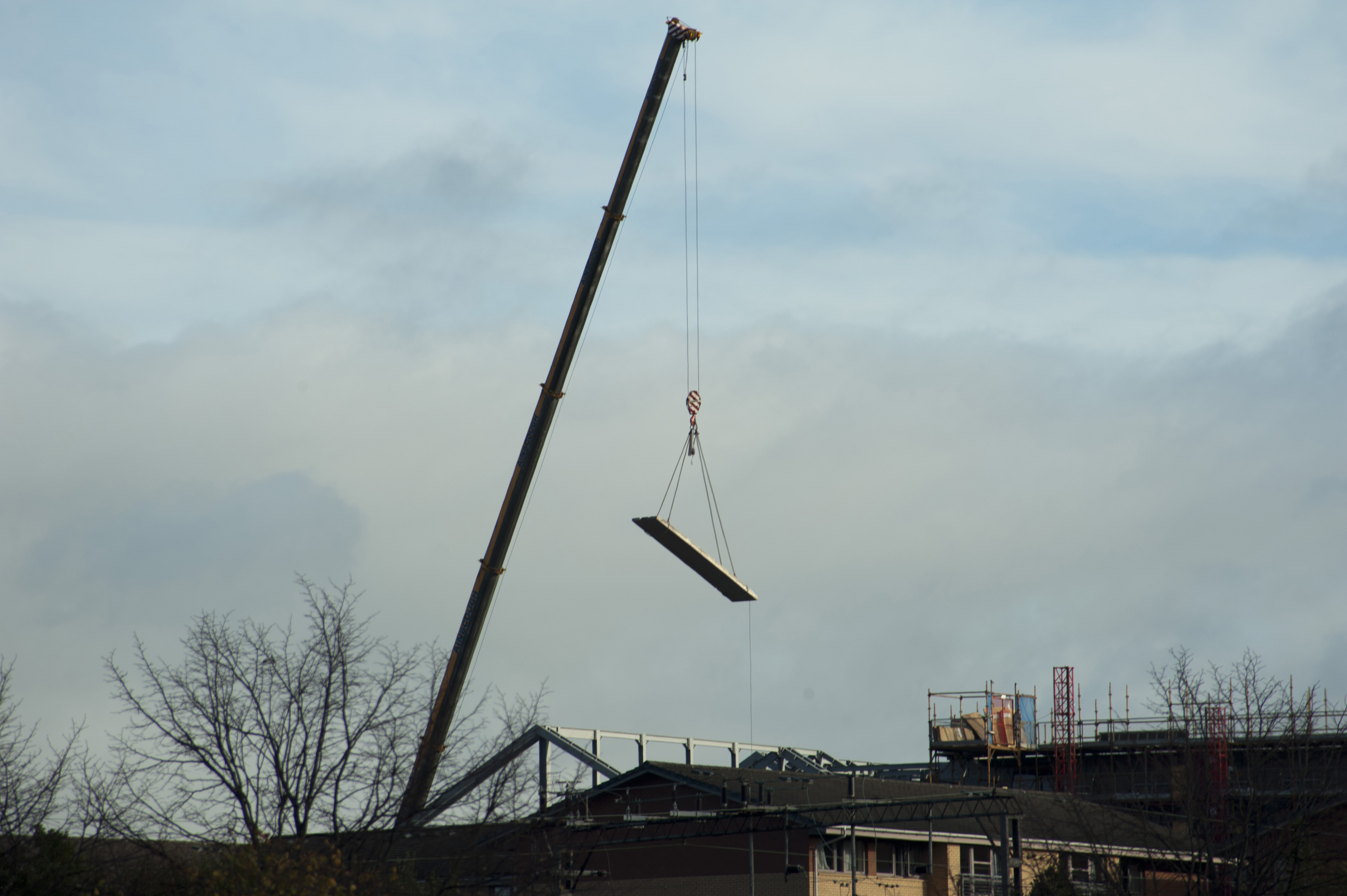 Industrial crane lifting a load raising a beam at a construction site for a commercial building silhouetted against a cloudy sky