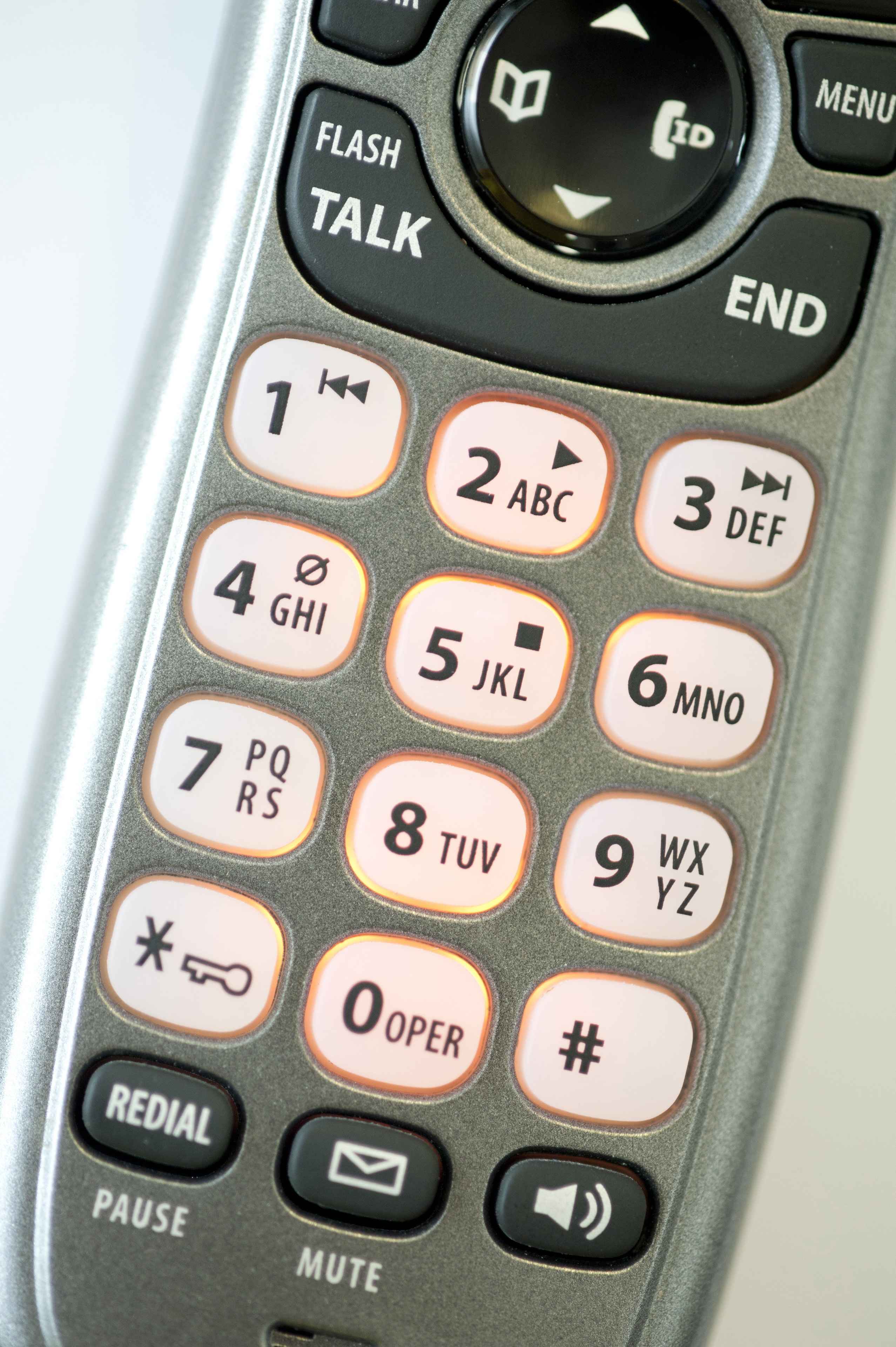Close up overhead view of the keypad and keys with their numbers and alphabet letters on a telephone handset in a telecommunications concept