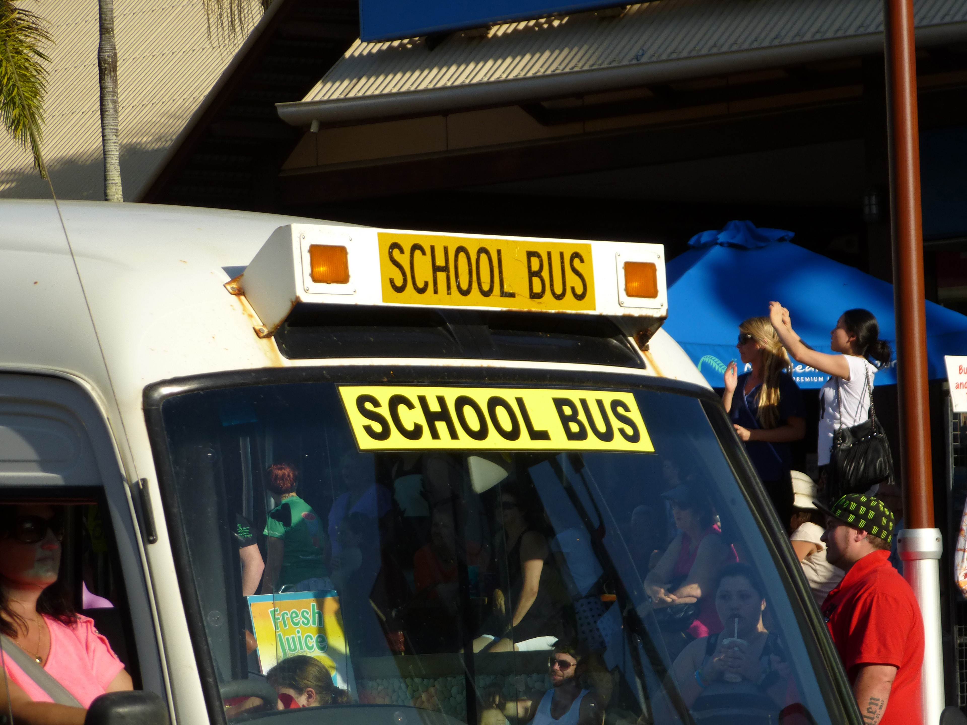 Front windscreen and yellow sign on a school bus with students visible in the background and in the bus
