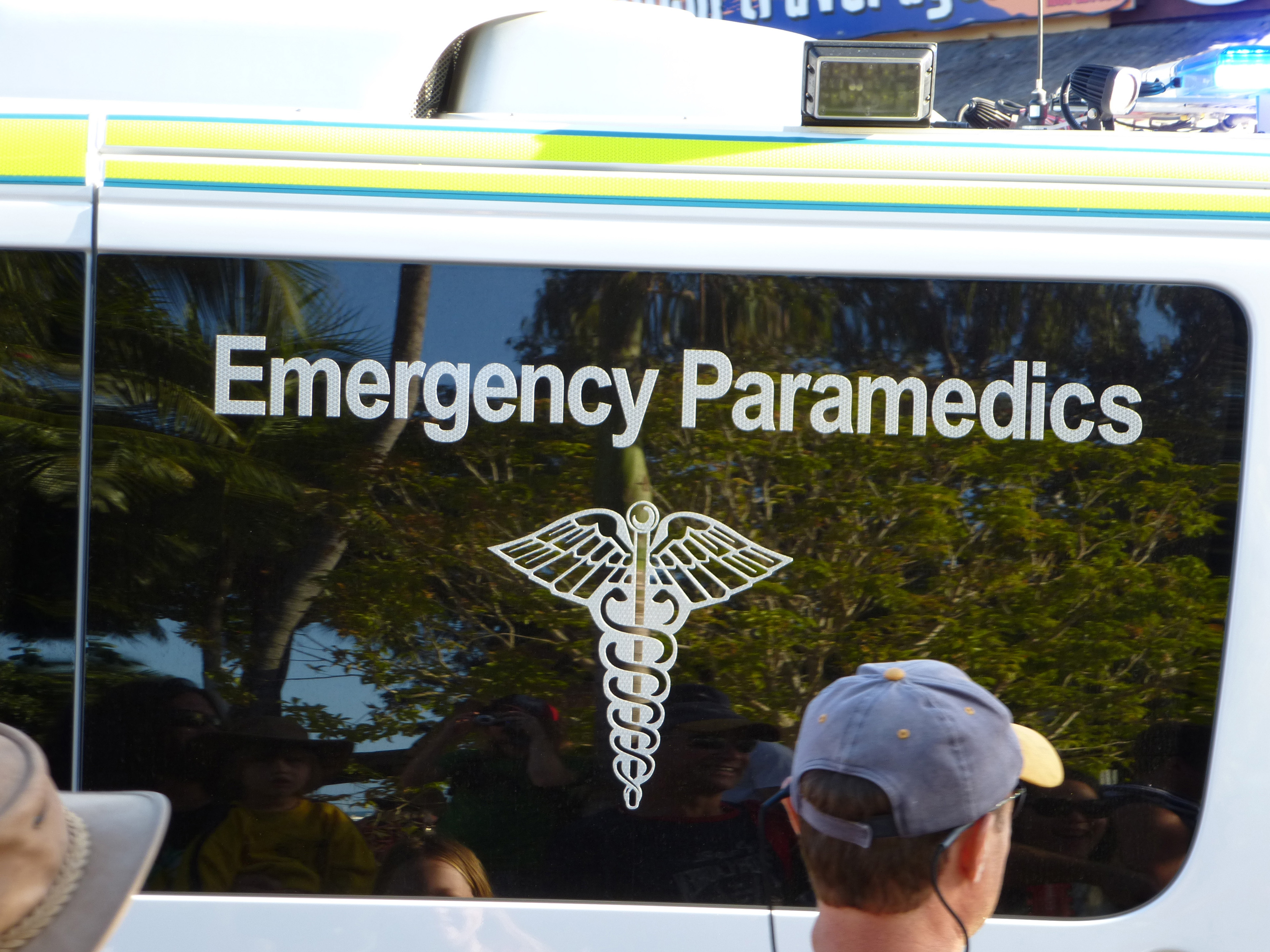 Emergency services sign for Emergency Paramedics with the medical caduceus on the window of a response vehicle with the back of peoples heads standing watching in the foreground