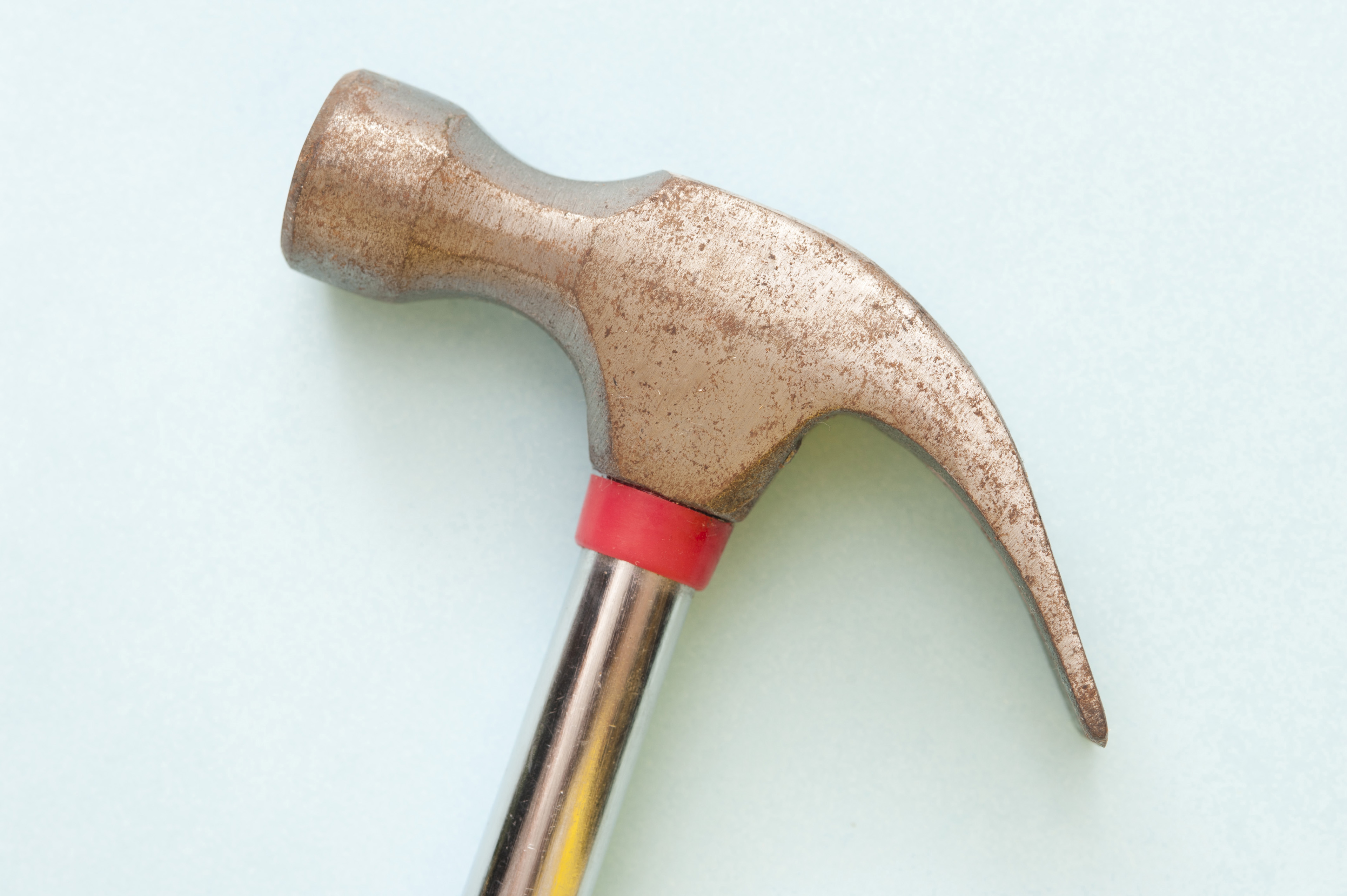Side view of the head of a claw hammer on a white background in a woodworking, construction and DIY concept
